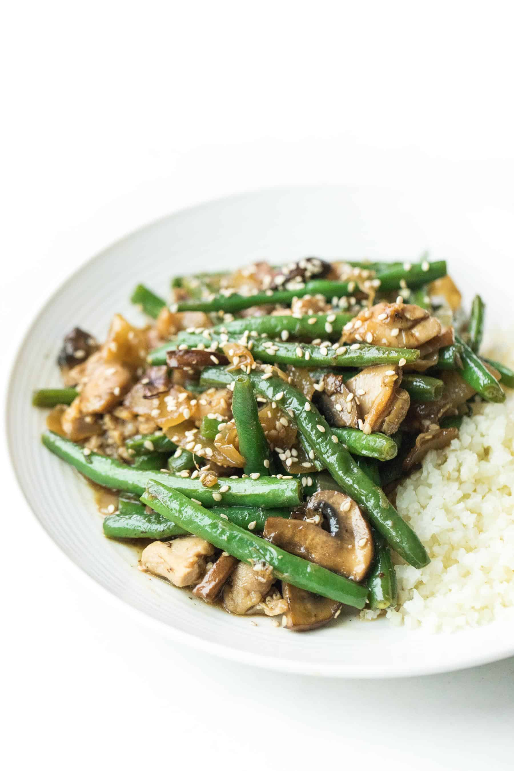 sesame chicken green bean stir fry on a white plate with cauliflower rice
