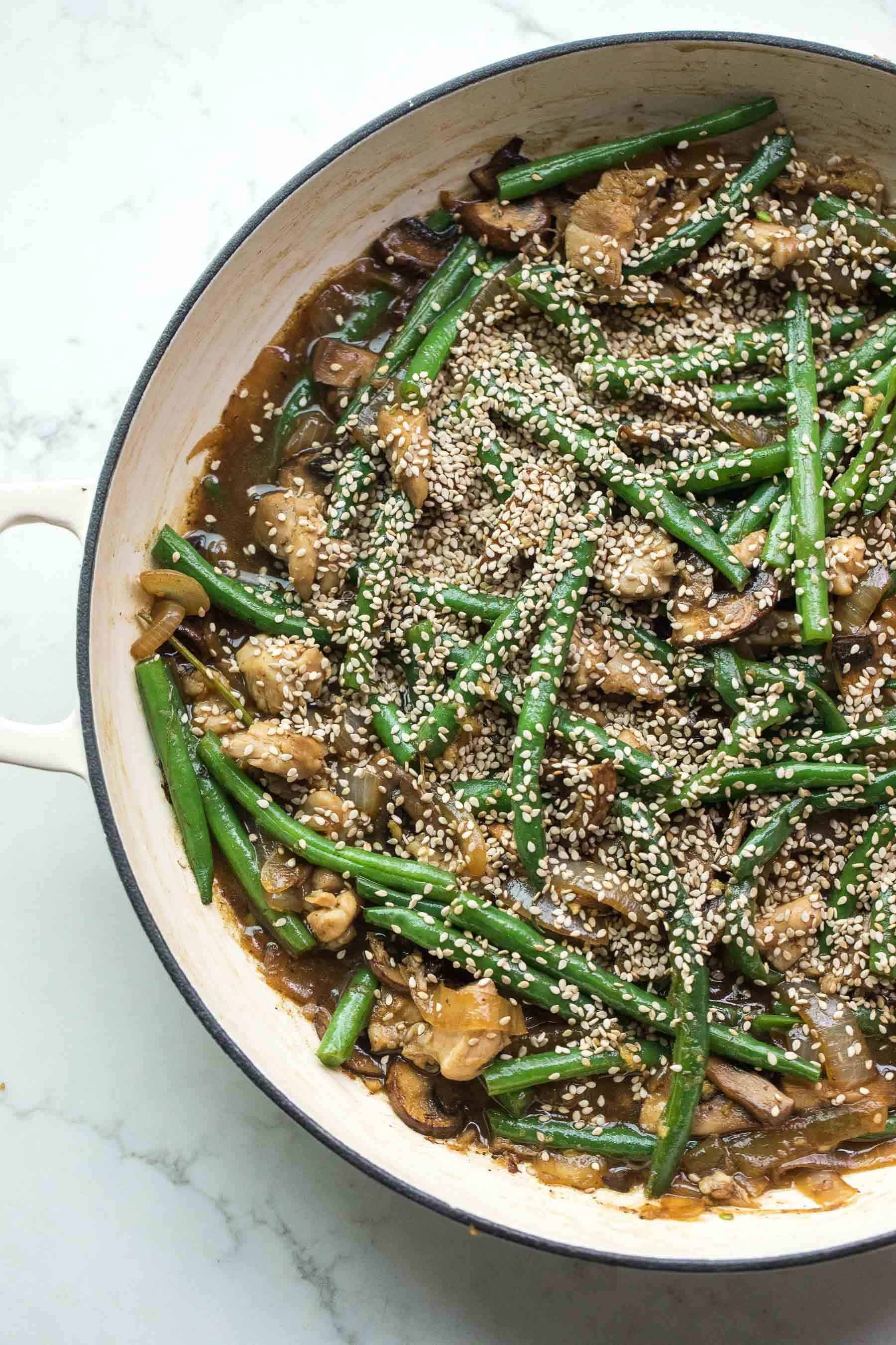sesame chicken green bean stir fry in a white pan