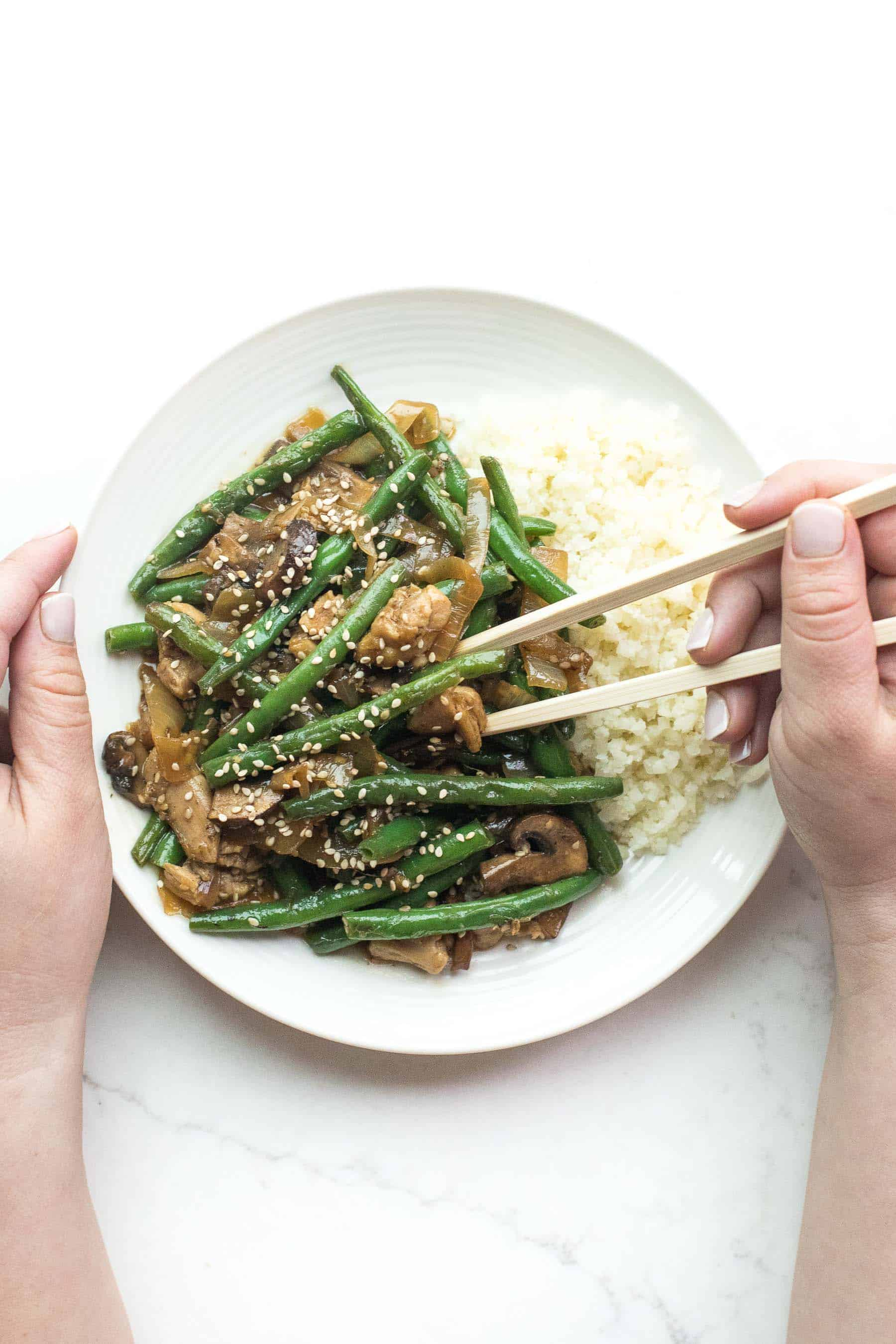 2 hands holding chopsticks to eat sesame chicken green bean stir fry