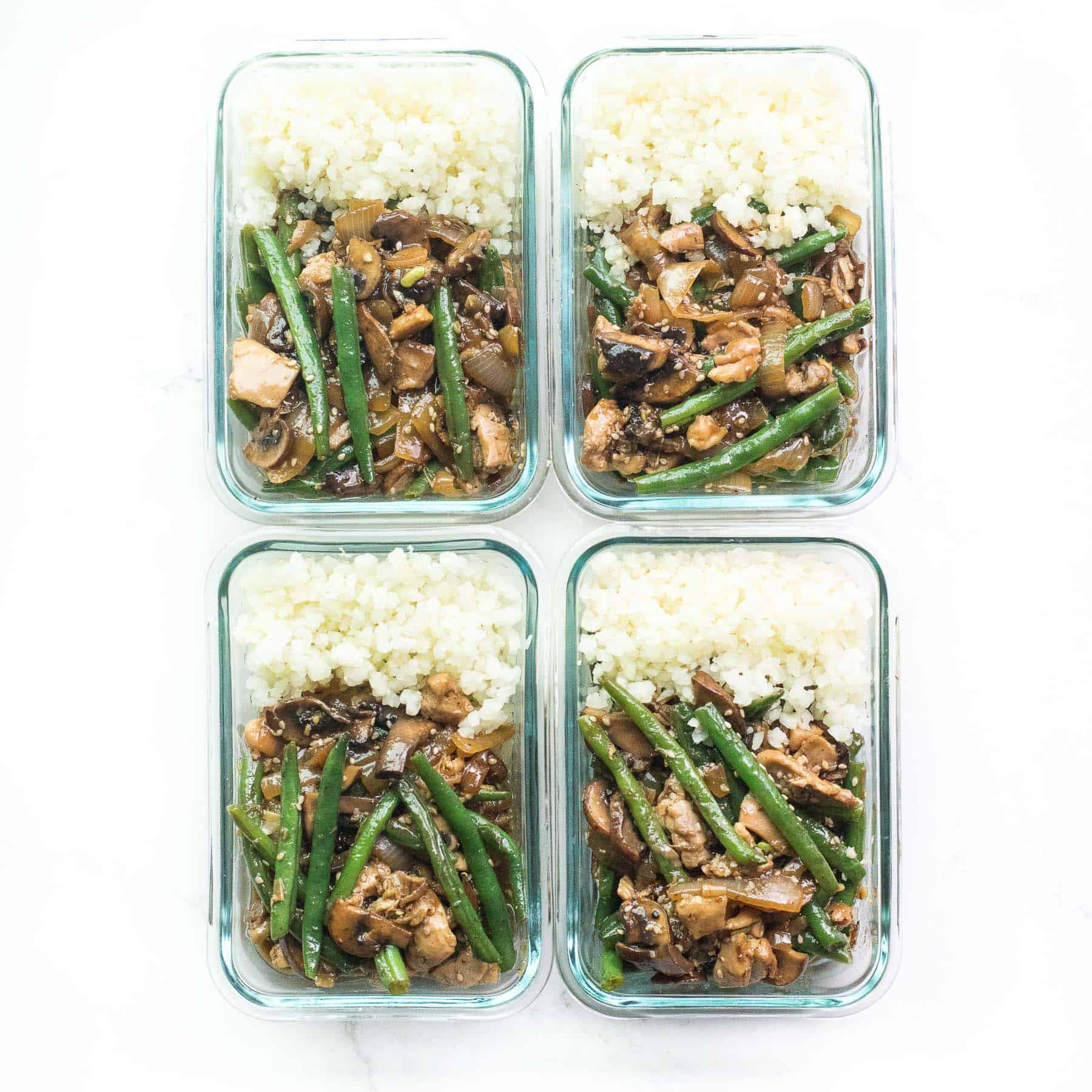 meal prep containers holding sesame chicken green bean stir fry