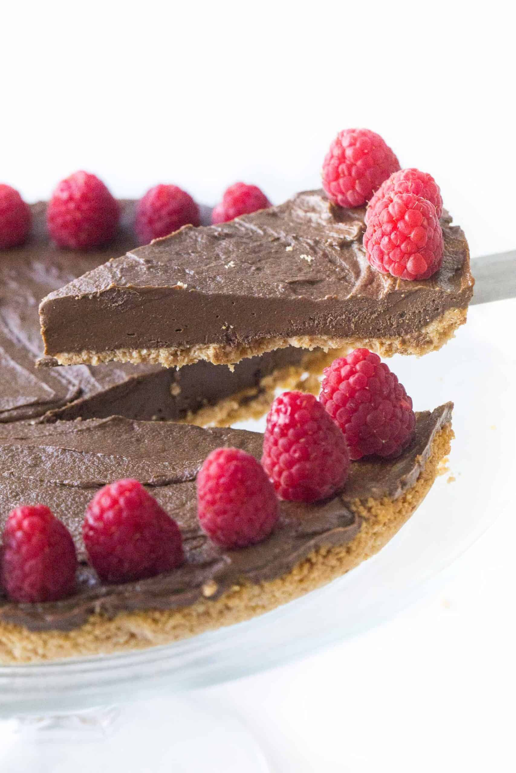 lifting a slice of healthy chocolate tart with raspberries
