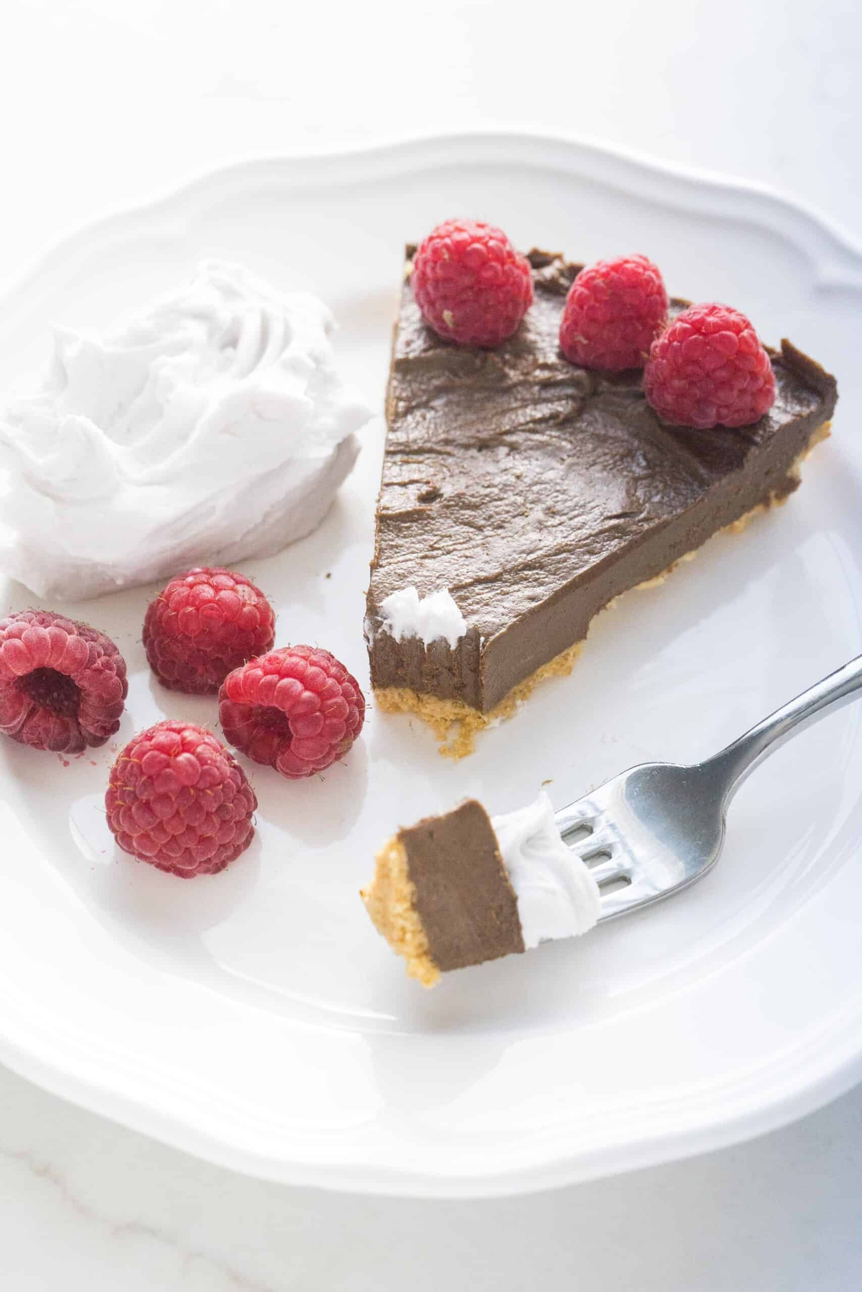 fork taking a bite out of healthy chocolate tart with raspberries and coconut whipped cream