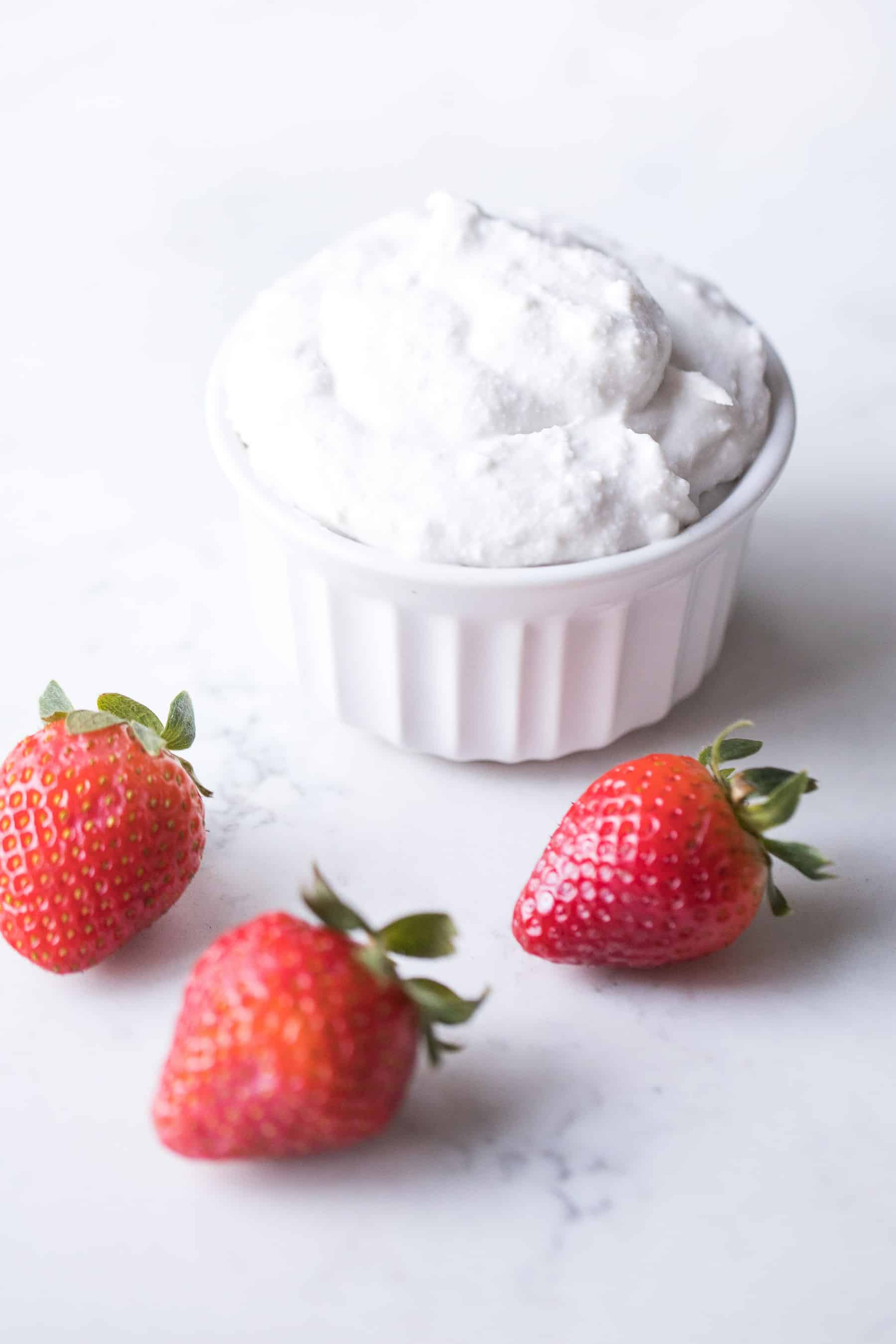 a white bowl of coconut whipped cream with strawberries in the background