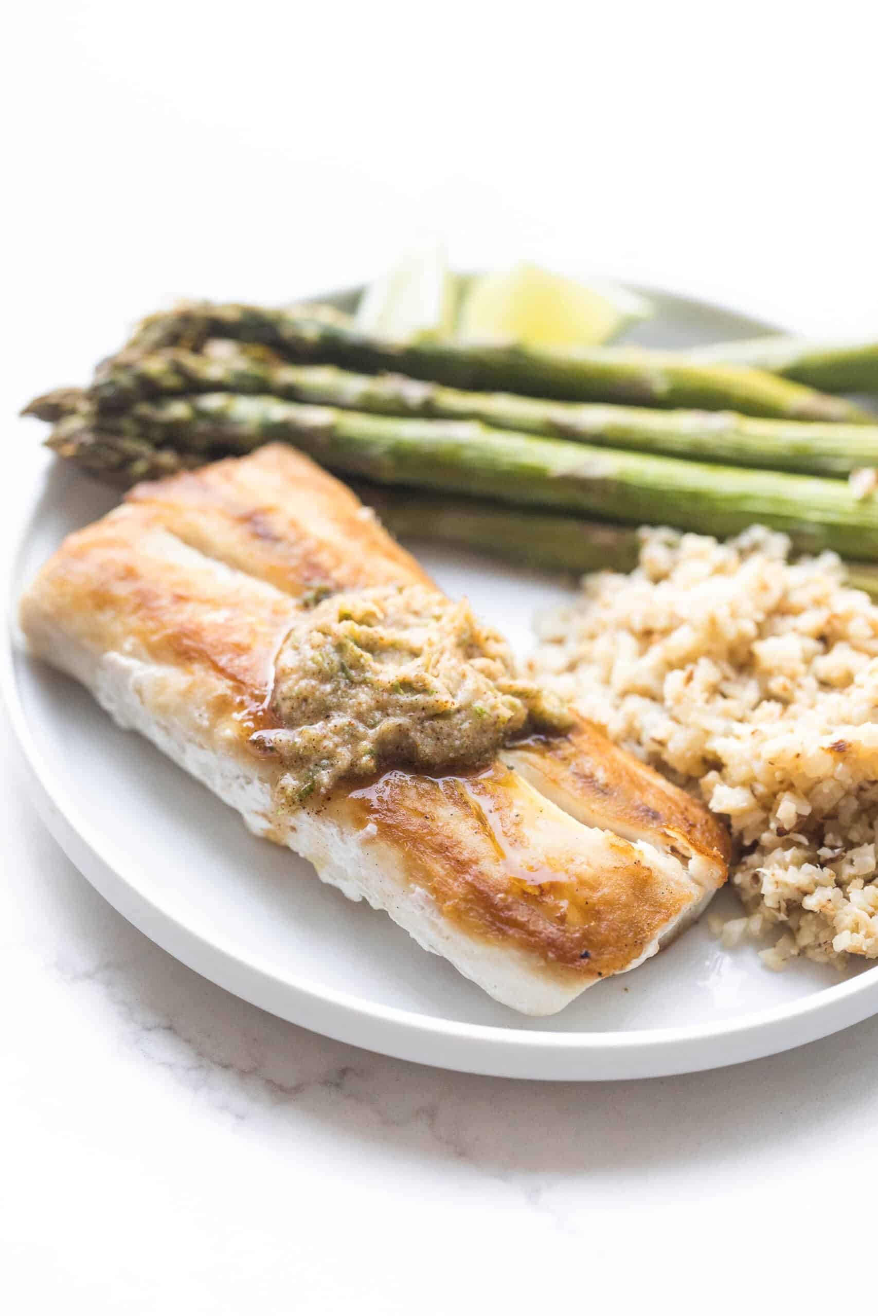 MAHI MAHI WITH CHILI LIME COMPOUND BUTTER WITH CAULIFLOWER RICE AND ASPARAGUS ON A WHITE PLATE AND BACKGROUND