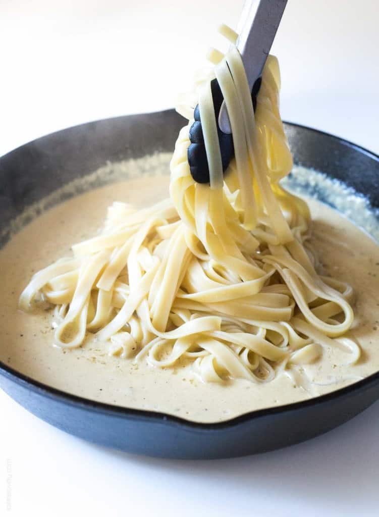 Noodles being dipped in homemade alfredo sauce in a cast iron skillet