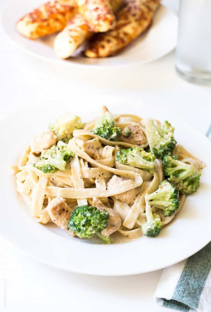 Broccoli chicken fettucine alfredo on a white plate
