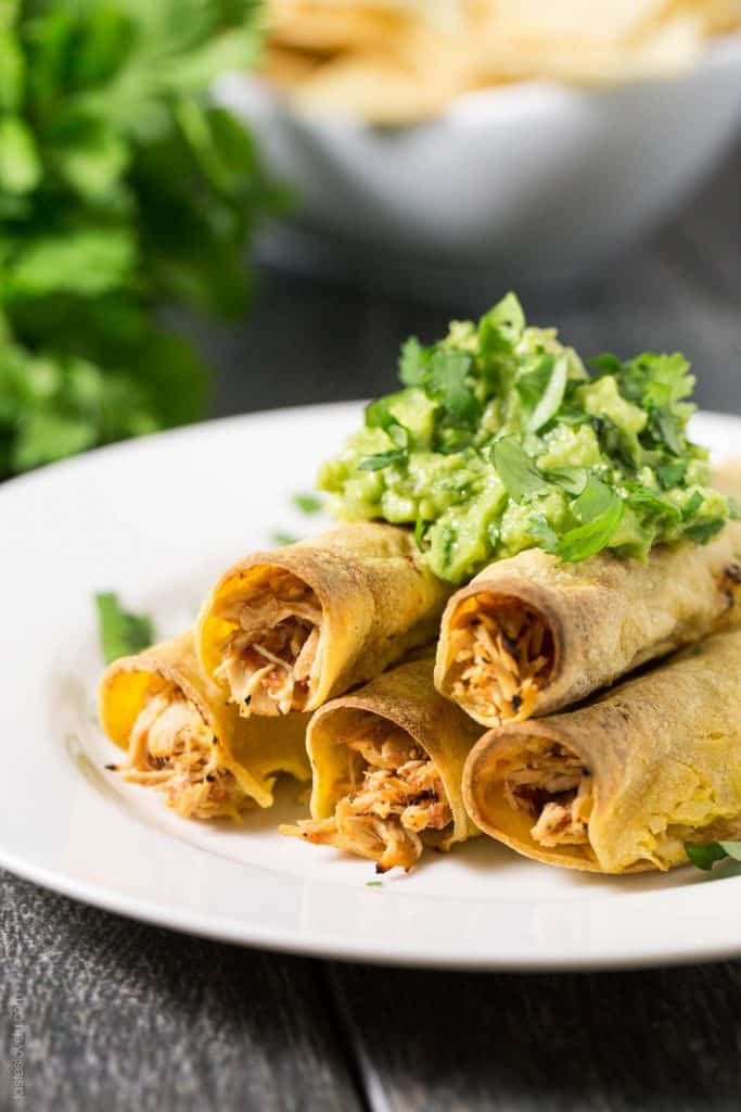 Baked Shredded Chicken Taquitos - juicy Mexican shredded chicken made in the slow cooker, then wrapped in corn tortillas, sprayed with olive oil, and baked in the oven. Great for an appetizer or dinner, and much healthier than fried!