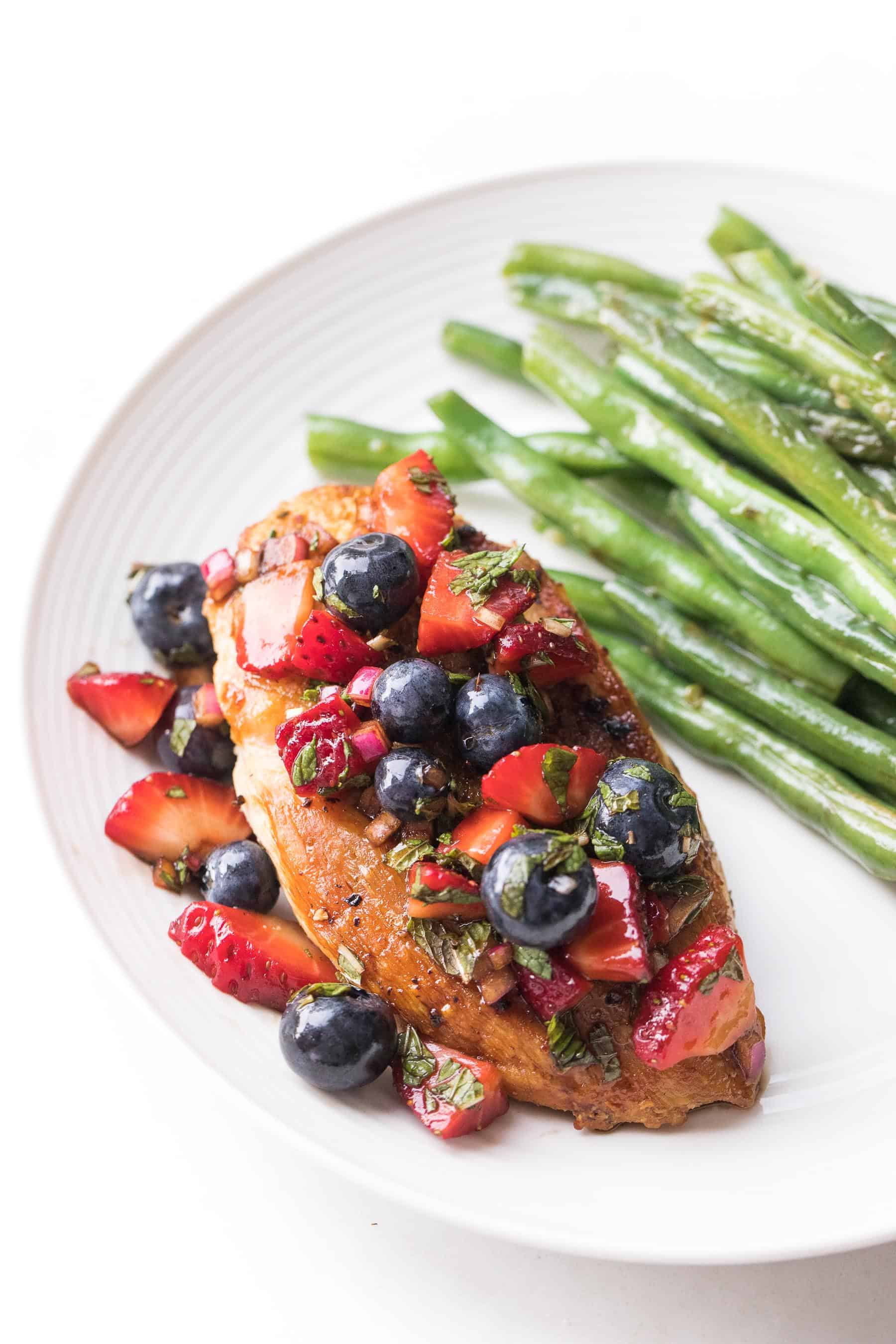 chicken topped with blueberry and strawberry salsa on a white plate and a white background