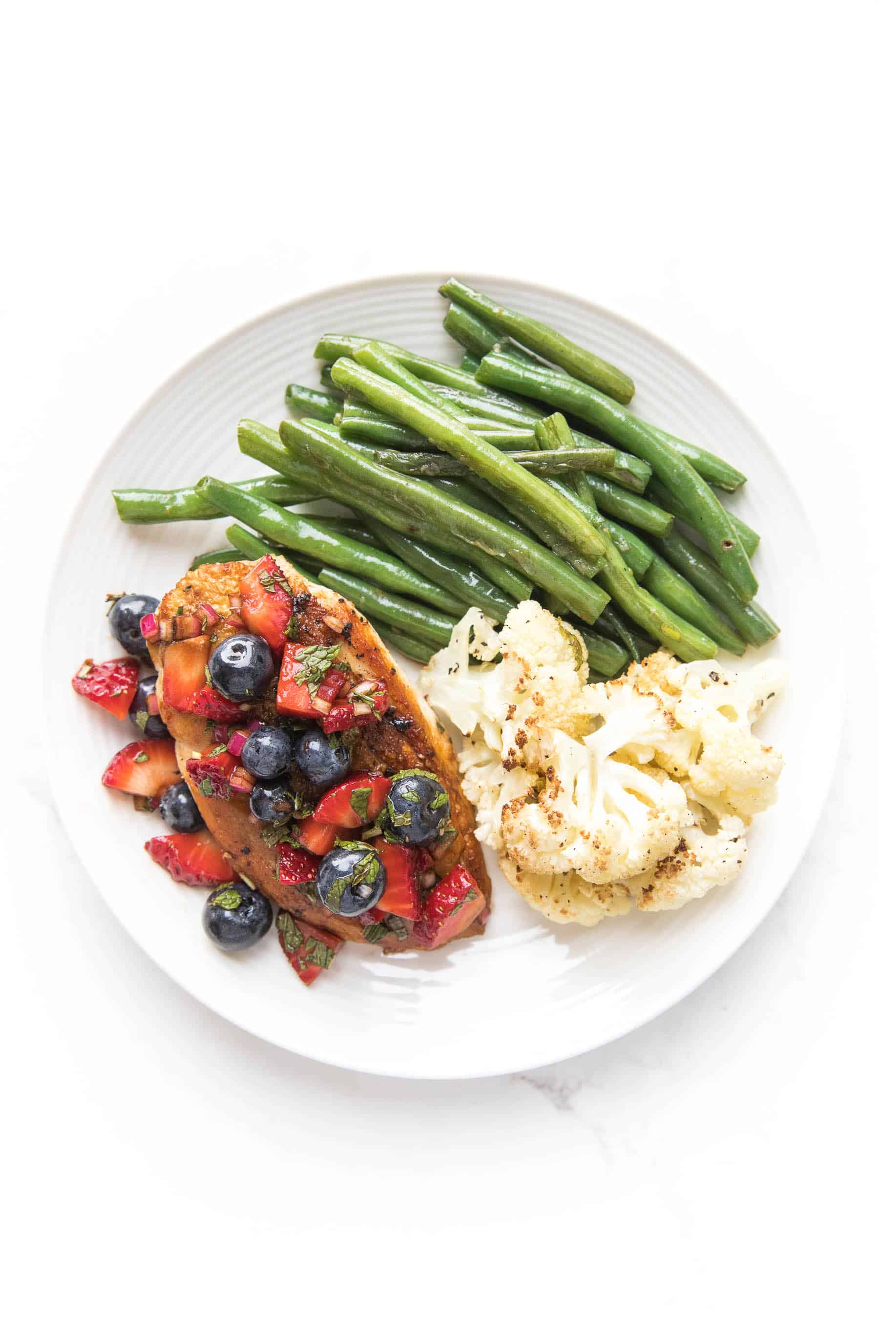 chicken topped with blueberry and strawberry salsa on a white plate and a white background with green beans and cauliflower