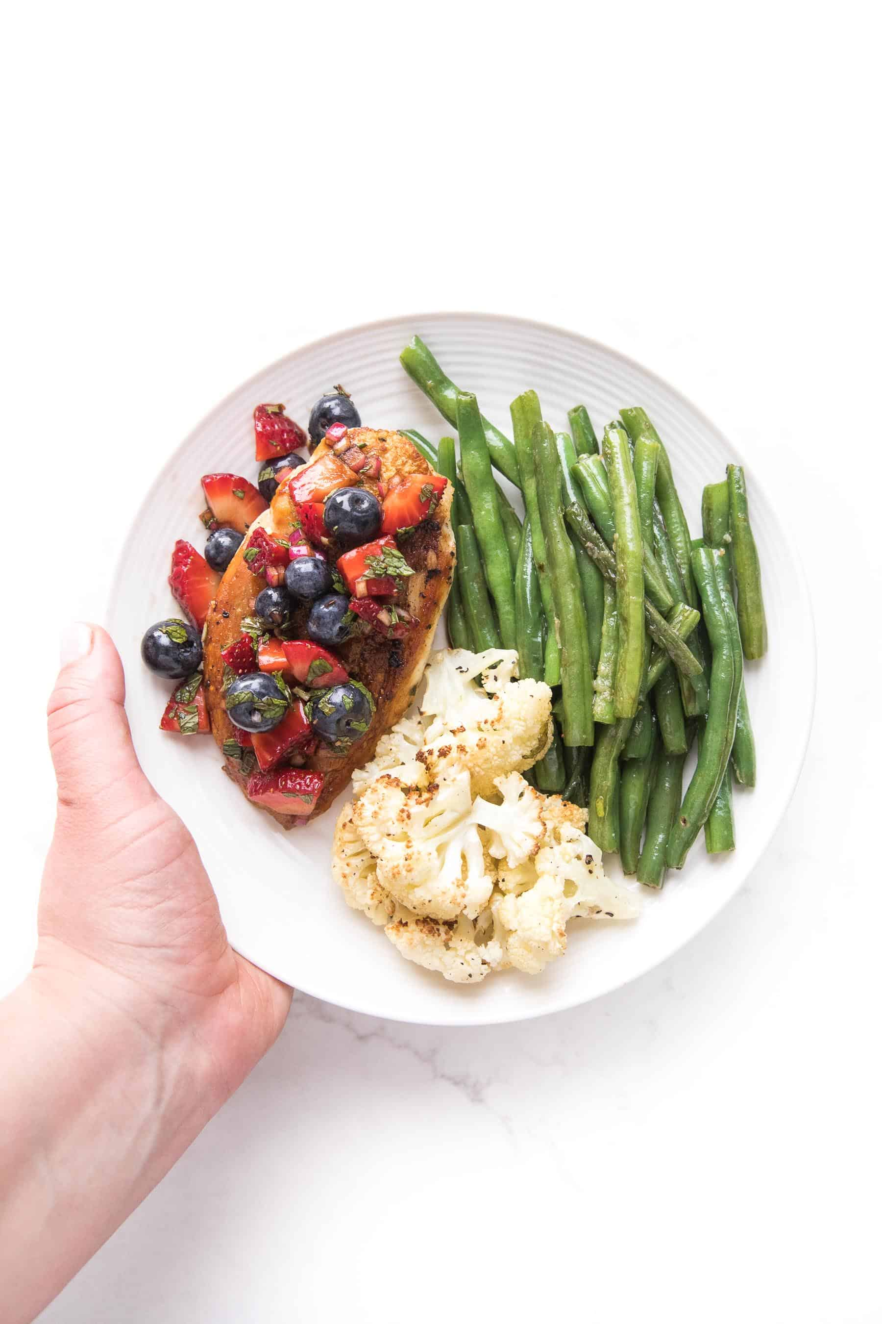 a hand holding chicken topped with blueberry and strawberry salsa on a white plate and a white background