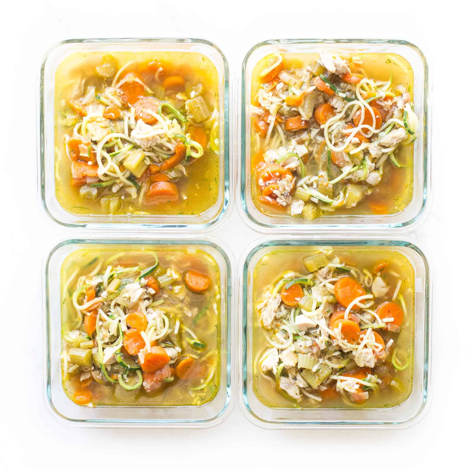 chicken zoodle soup in meal prep containers on a white background