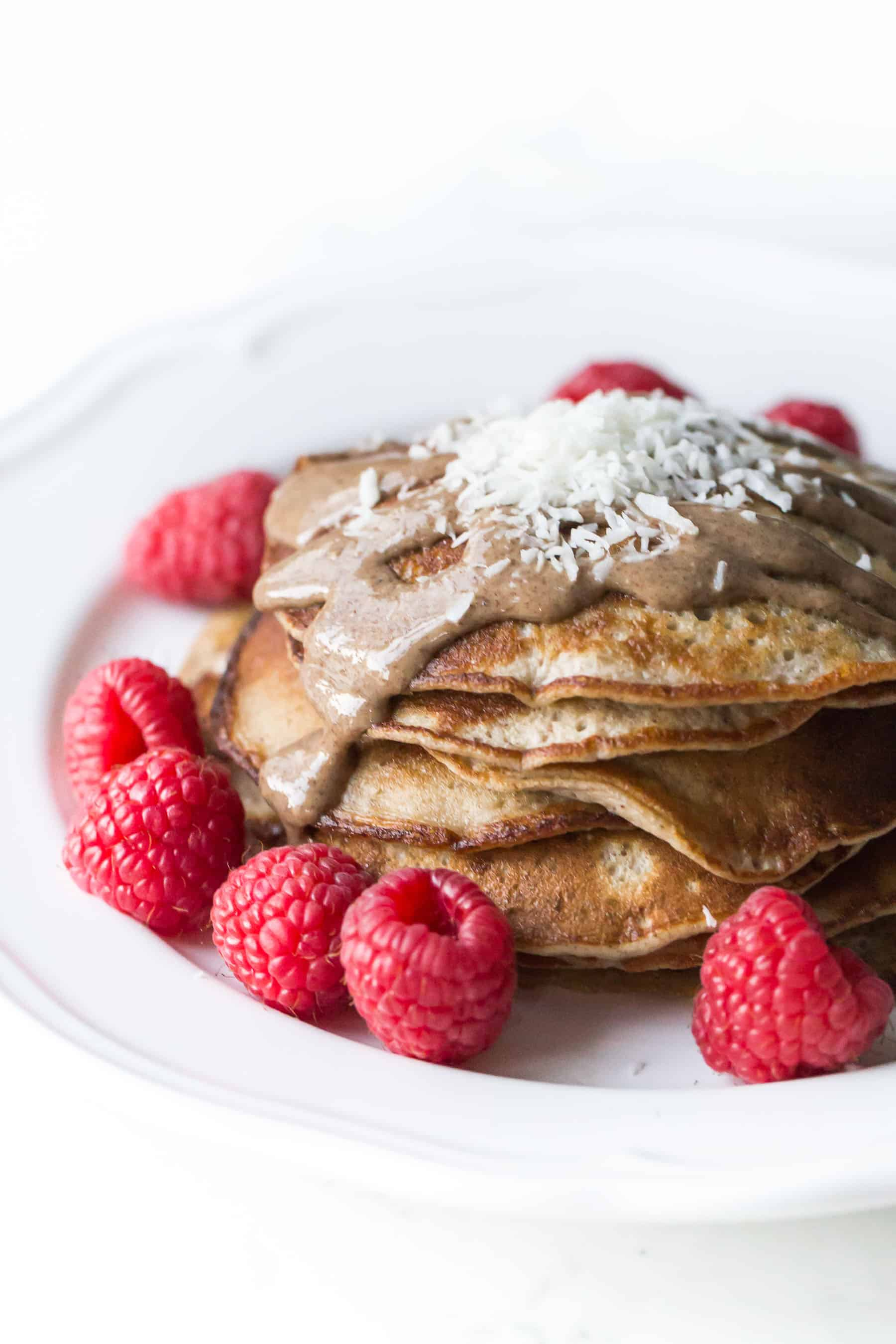 pancakes on a white plate topped with almond butter, shredded coconut and raspberries