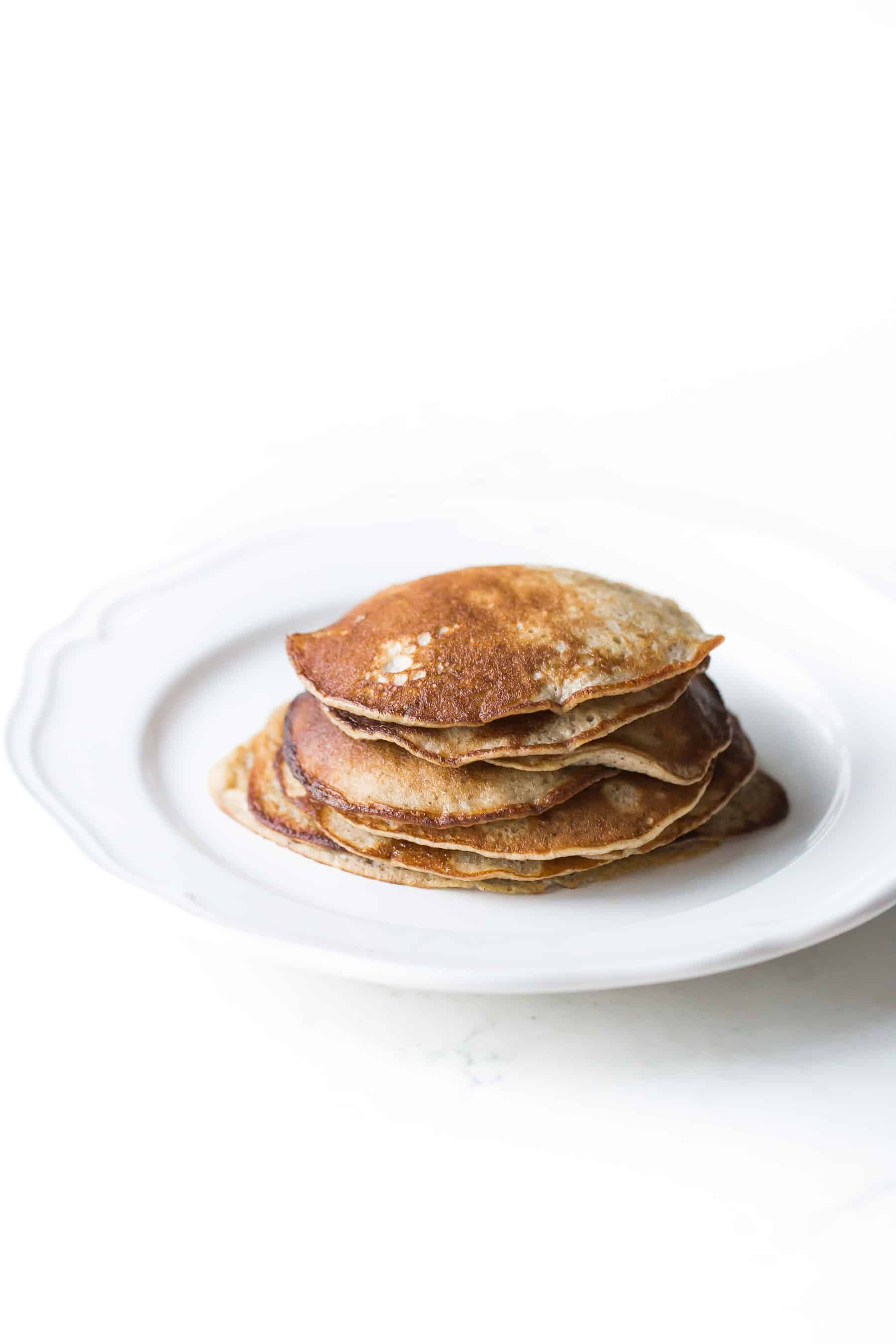 stack of small pancakes on a white plate