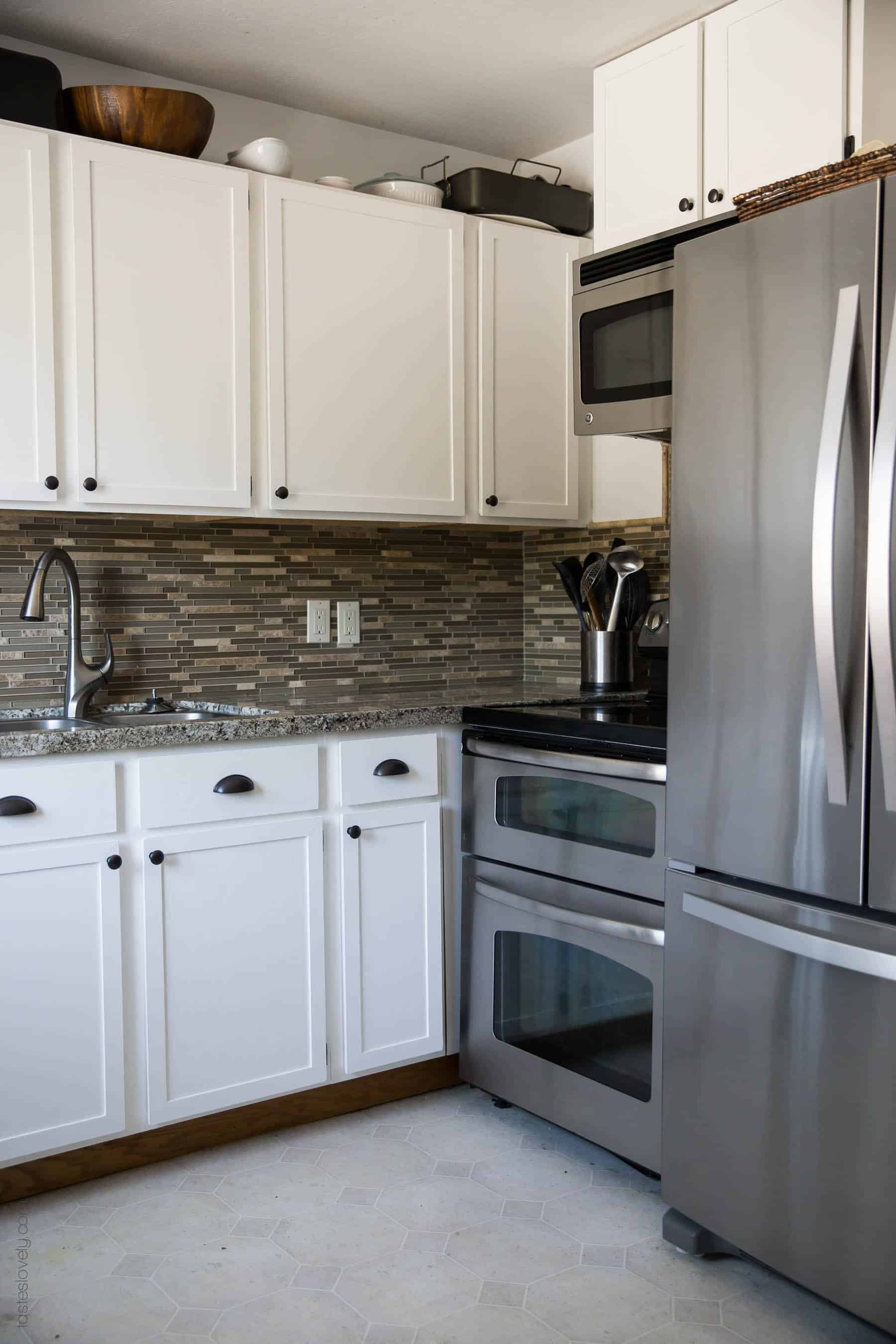 Our $281 DIY Kitchen Remodel - DIY painting oak cabinets white, adding wood trim to make shaker style cabinets, and adding hardware
