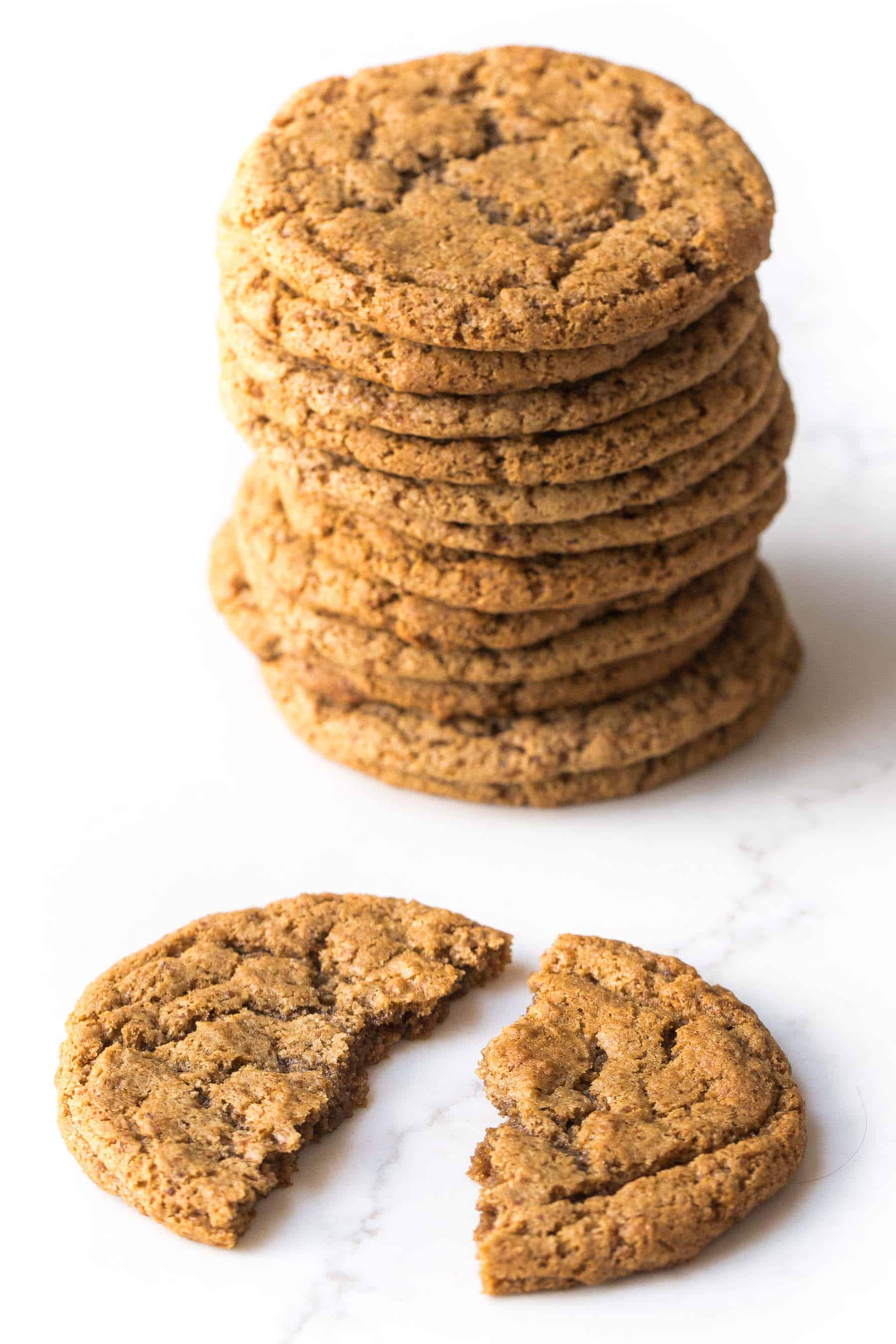 stack of almond butter cookies and 1 cracked cookie on a white background