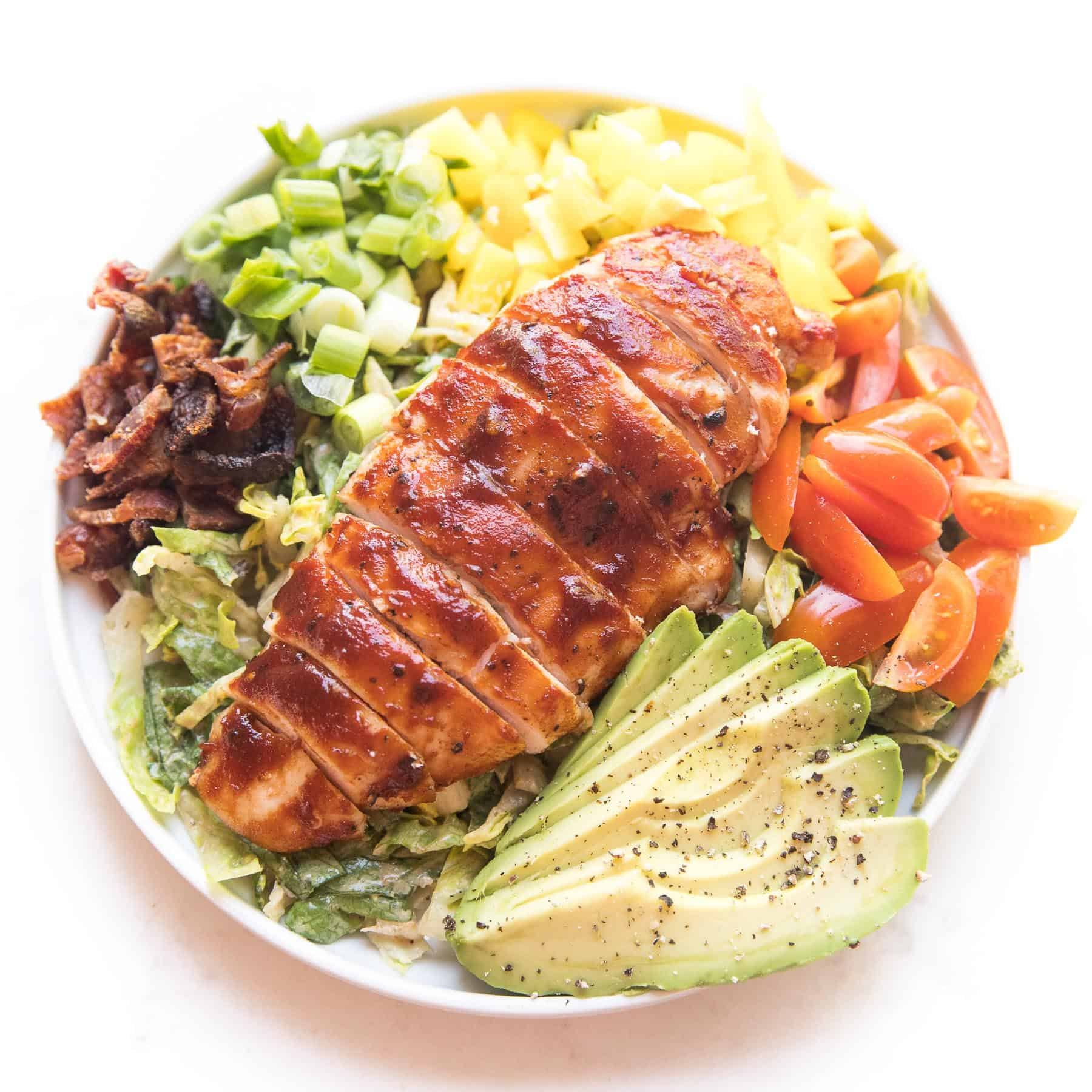 bbq chicken salad with avocado, bacon, bell pepper, tomatoes and green onions on a white plate and background