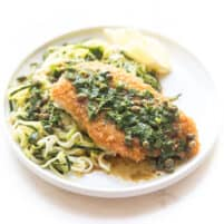 breaded lemon keto chicken piccata over zucchini noodles on a white plate and background