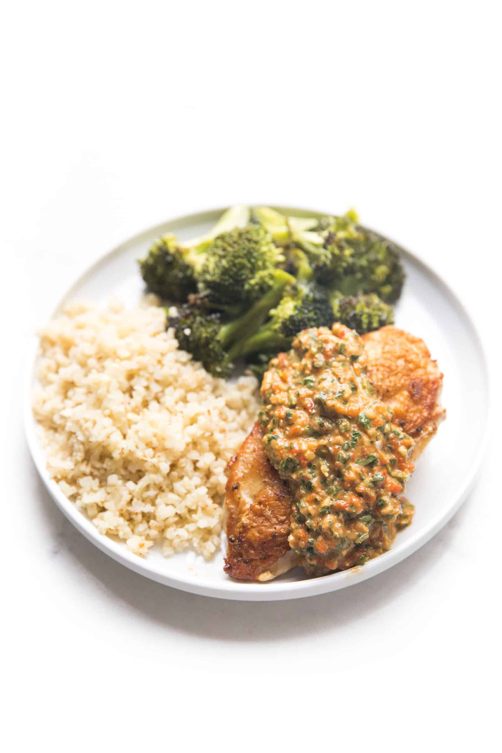 chicken topped with mediterranean salsa on a white plate with broccoli and cauliflower rice