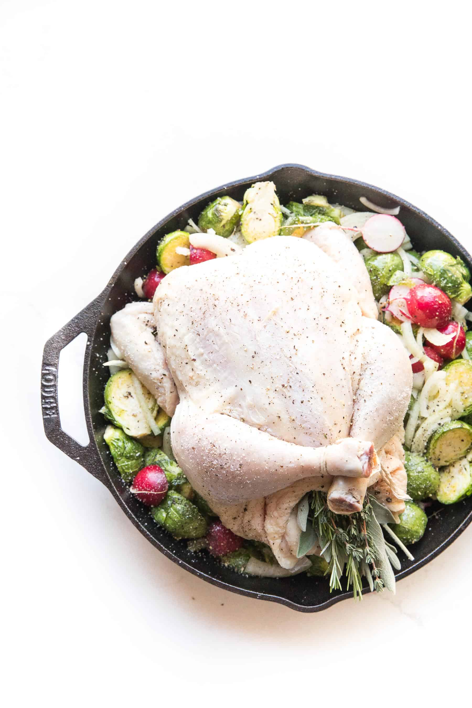 Whole30 + keto perfect roast chicken in a cast iron skillet with root vegetables