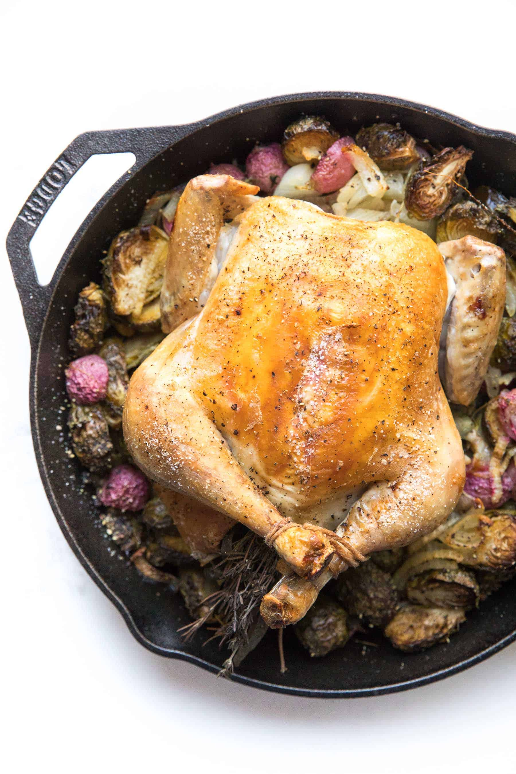 Roast chicken in a cast iron skillet with root vegetables