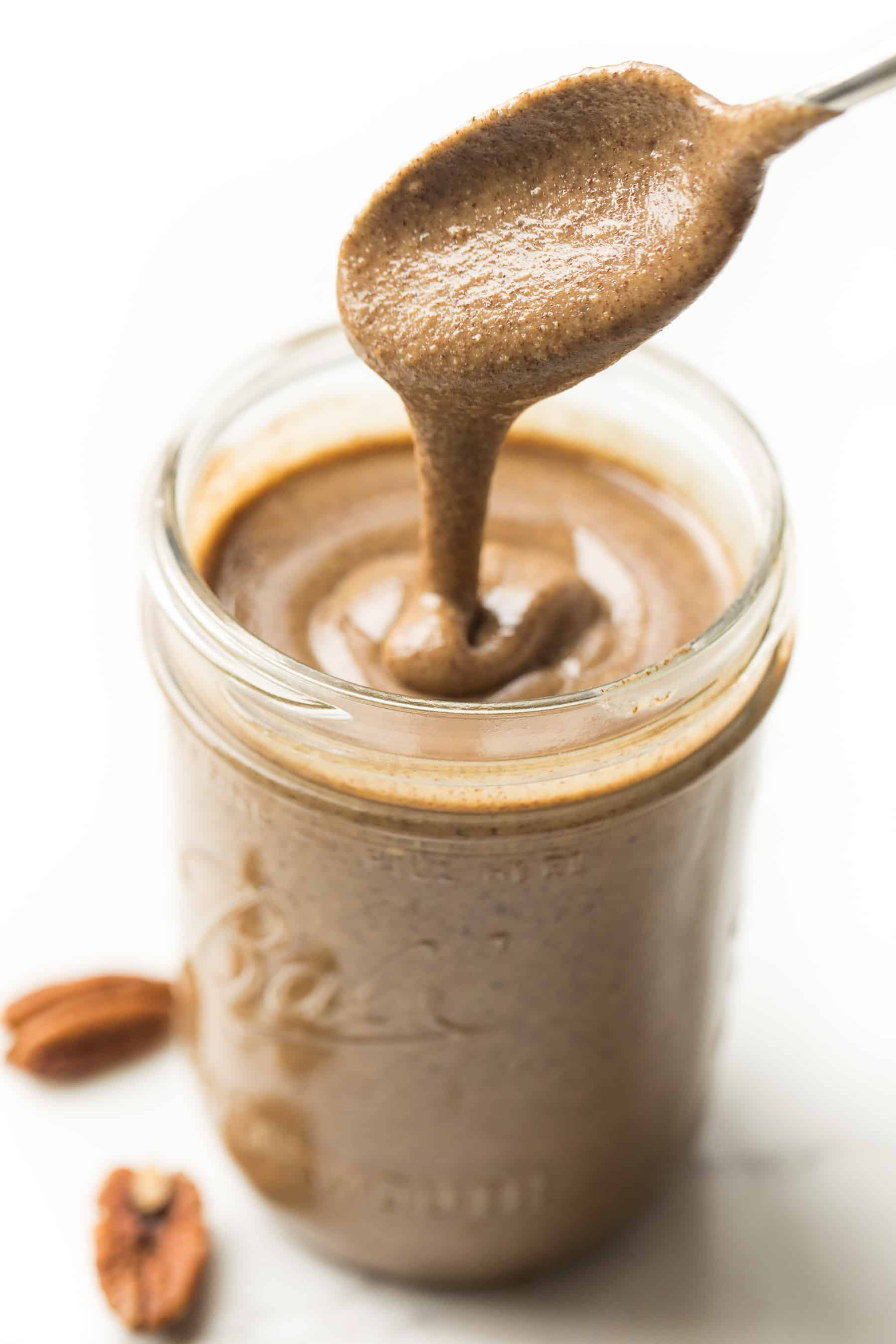 a spoon drizzling pecan butter into a mason jar