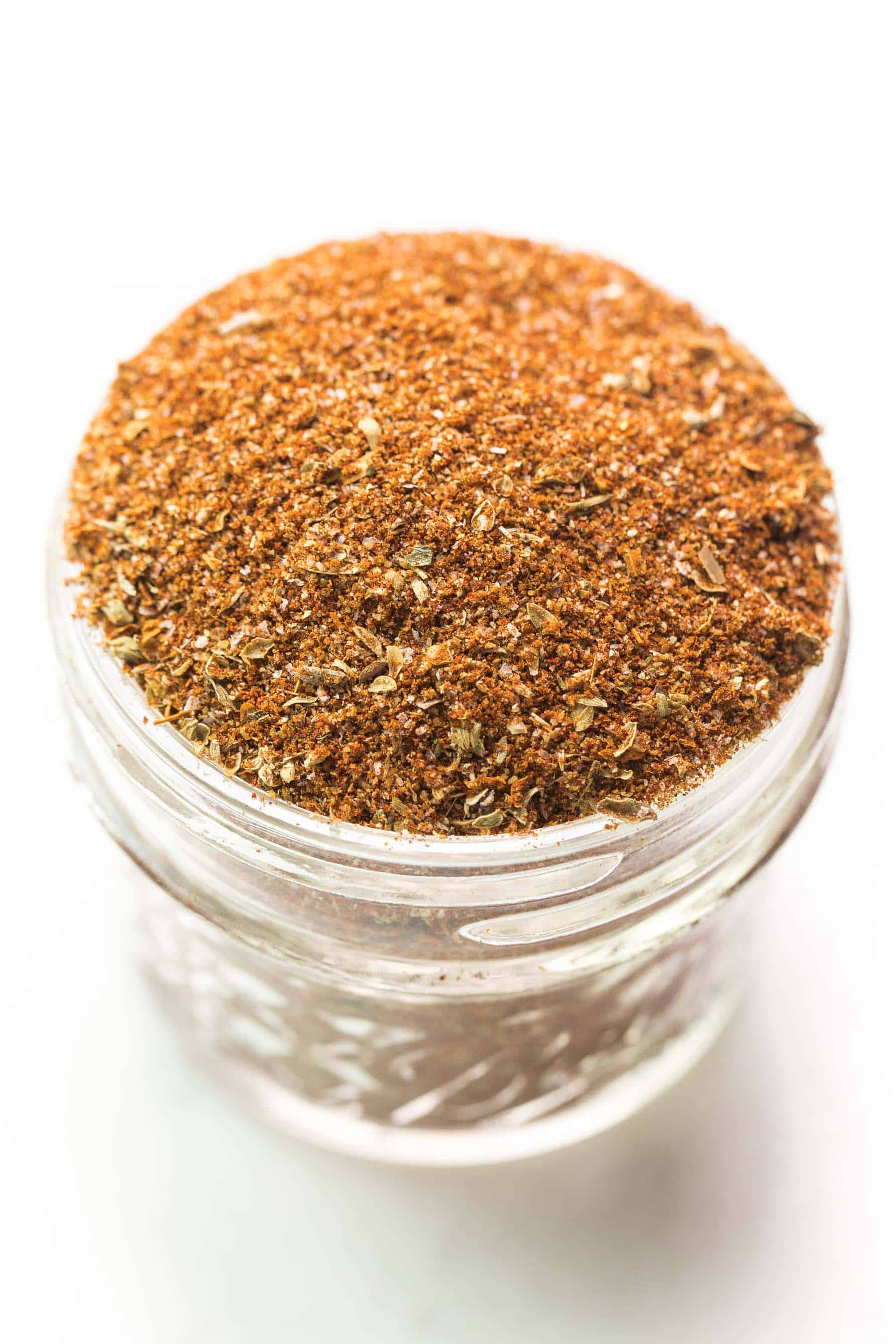 taco seasoning in a small mason jar on a white background