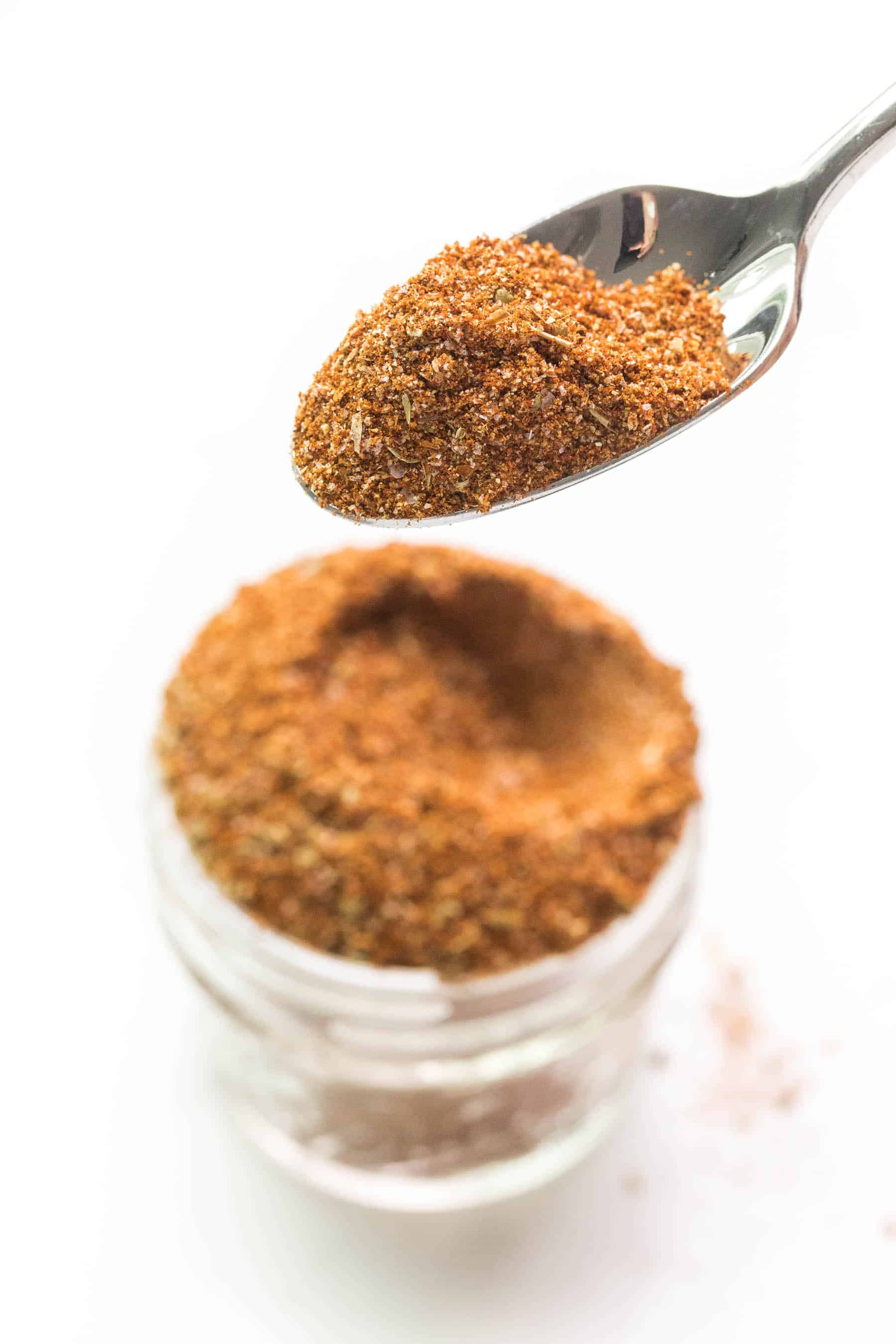 spoon holding taco seasoning on a white background