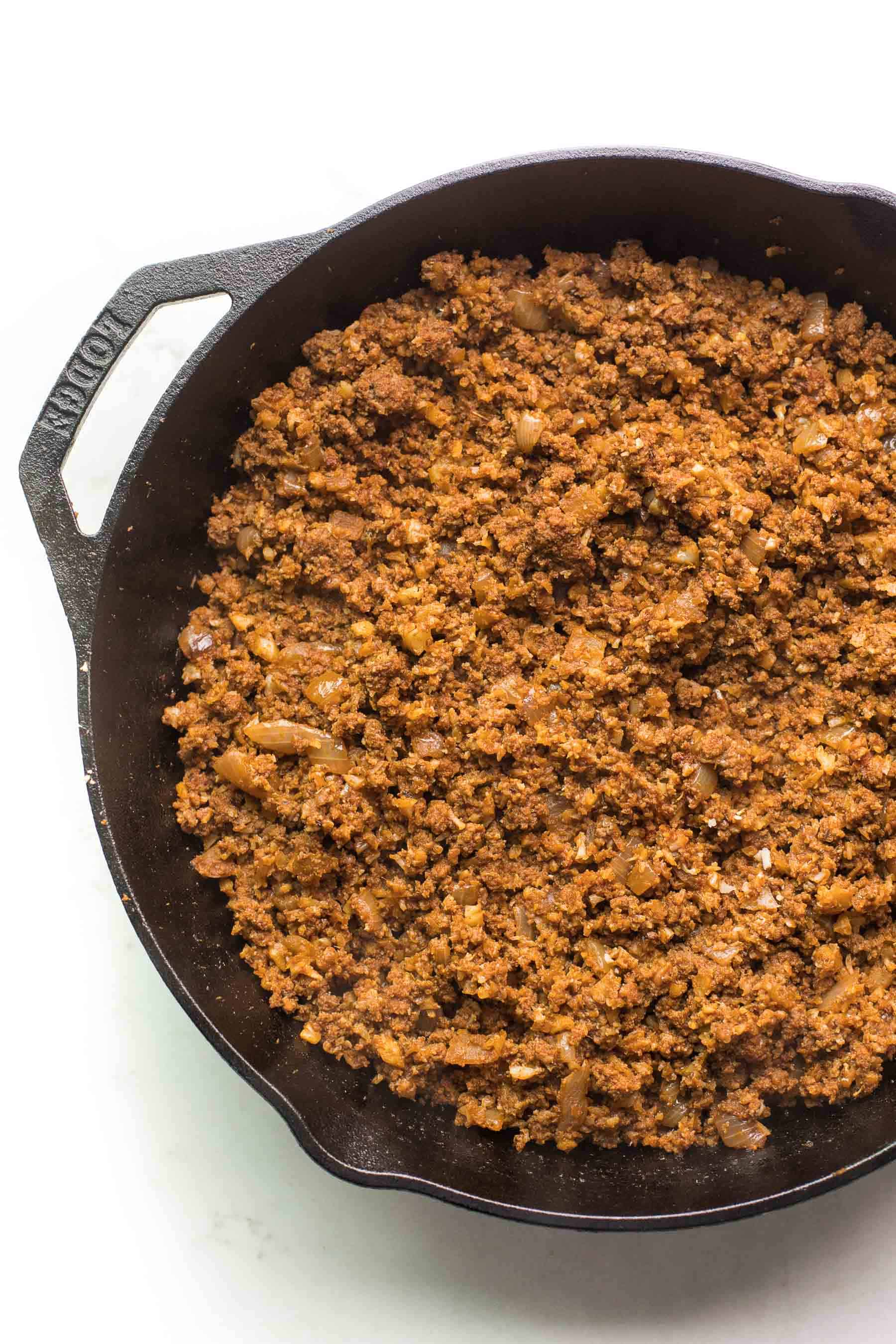 ground beef taco meat in a cast iron skillet on a white background