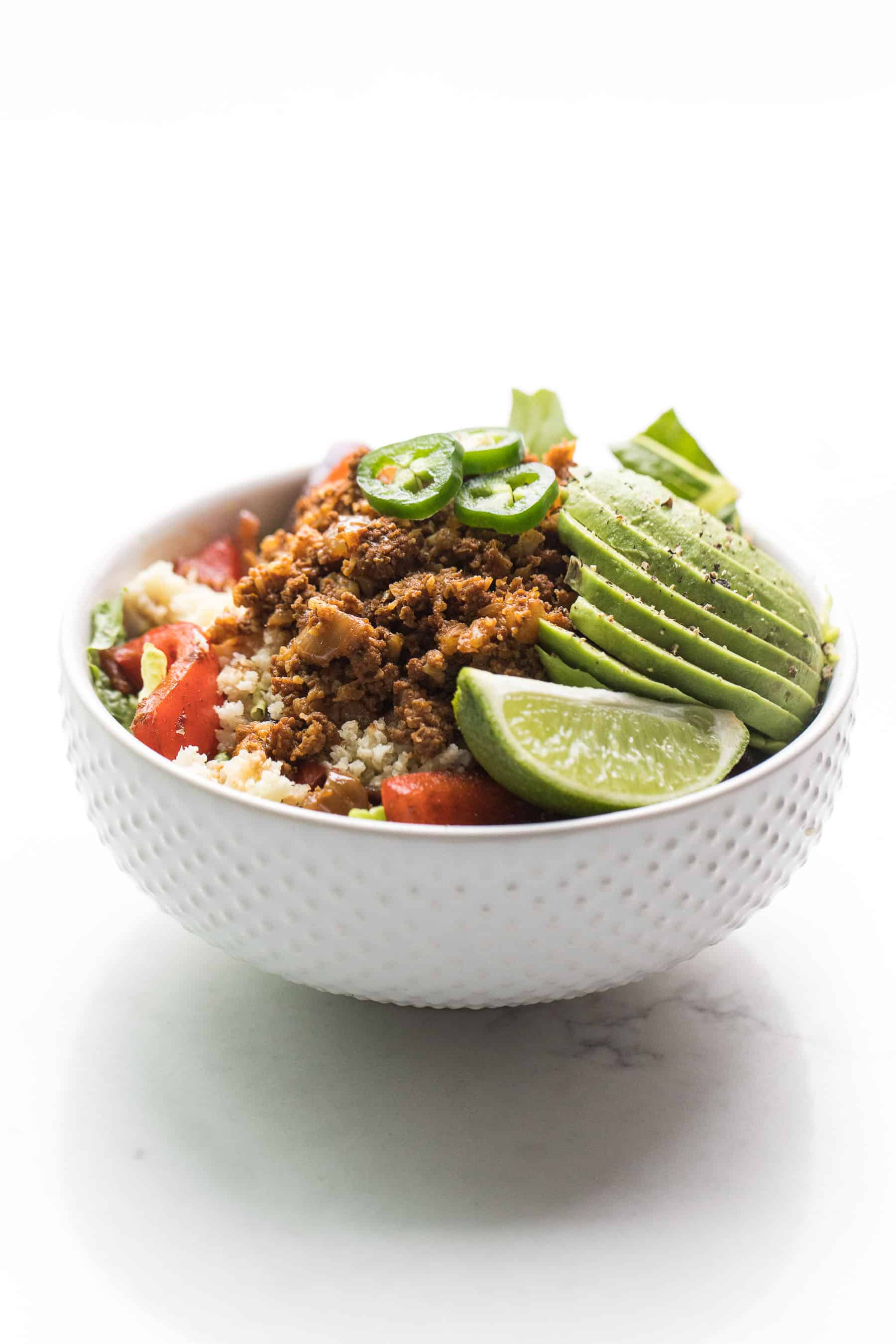 beef burrito taco bowl in a white bowl on a white background
