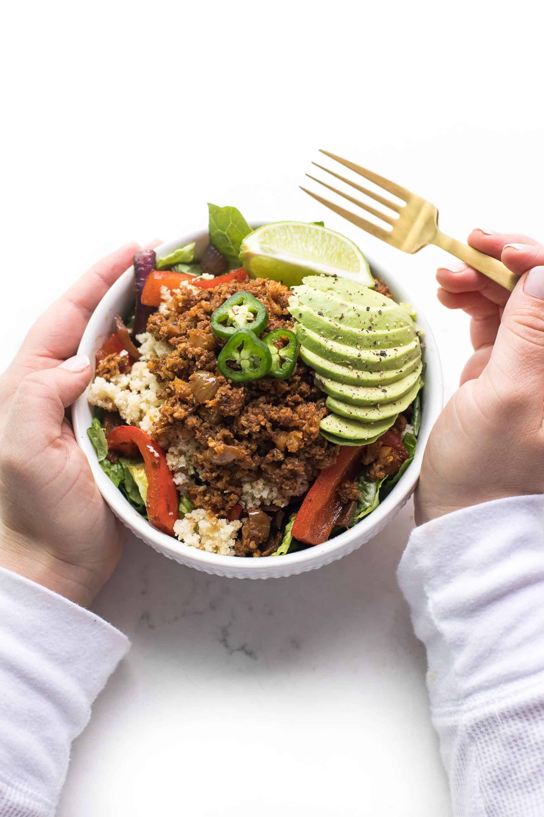 2 hands holding a beef burrito taco bowl in a white bowl on a white background