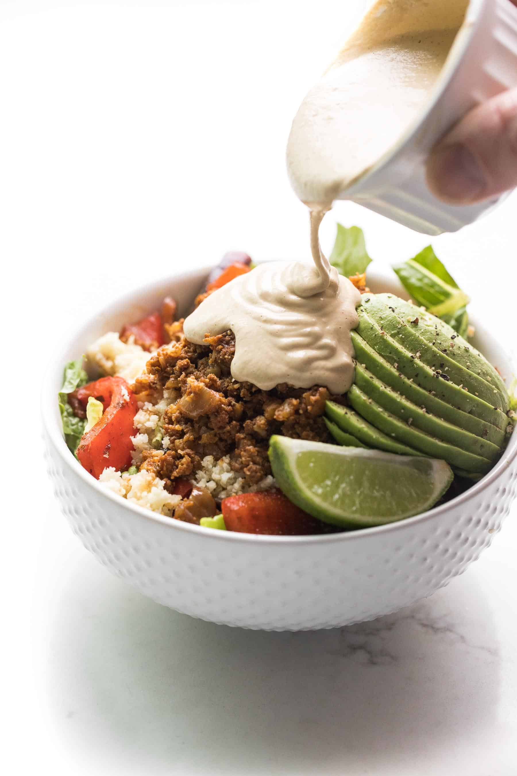 beef burrito taco bowl in a white bowl on a white background with cashew cheese queso poured on top