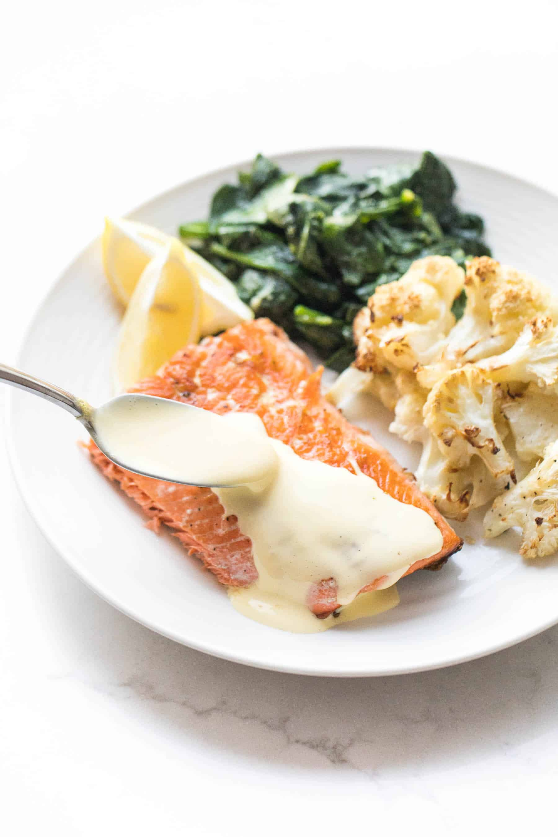 White plate with salmon and a spoon pouring hollandaise sauce, roasted cauliflower, sauteed spinach on a white background
