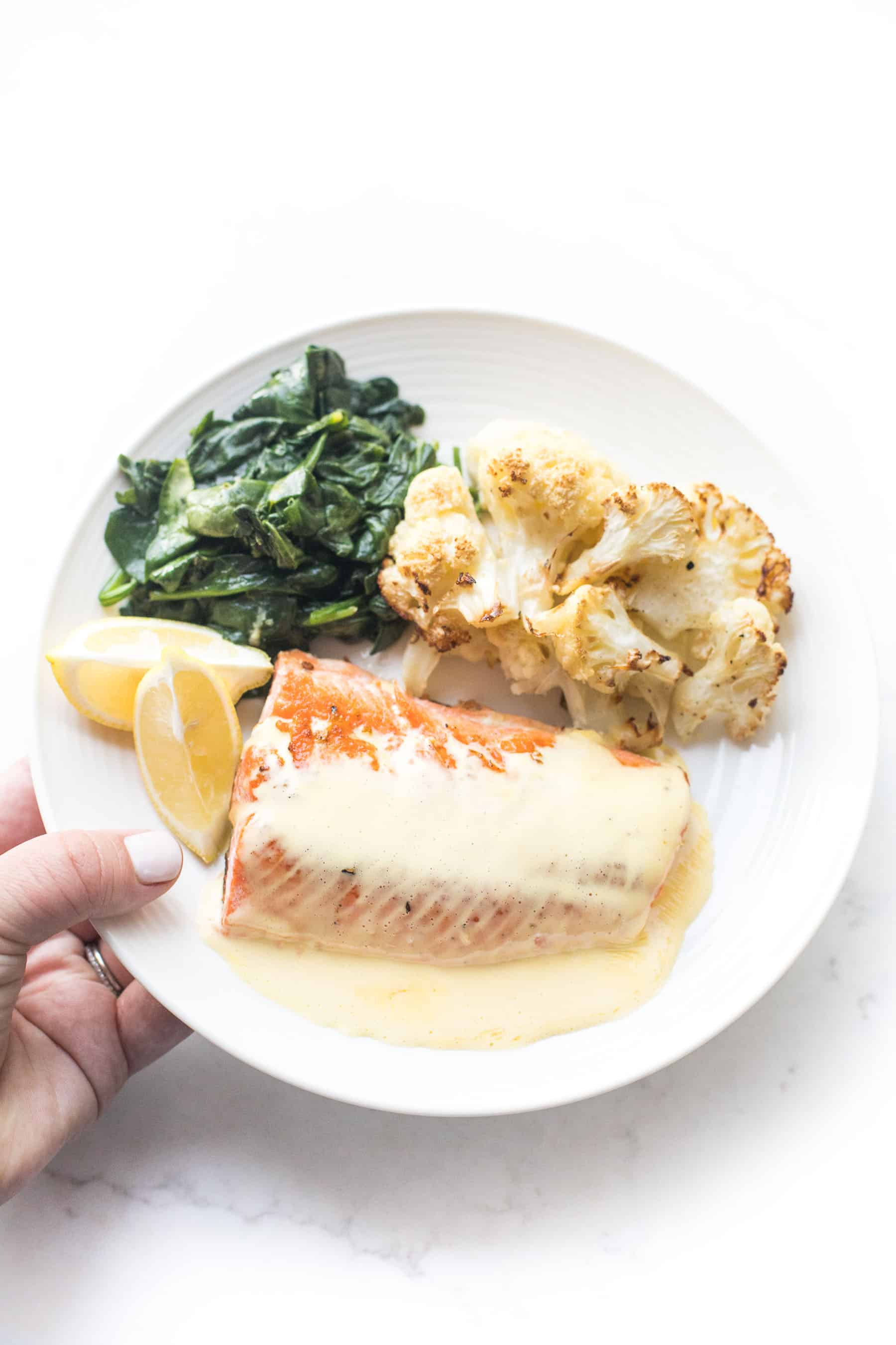 a hand holding a white plate with salmon and hollandaise sauce, roasted cauliflower, sauteed spinach on a white background