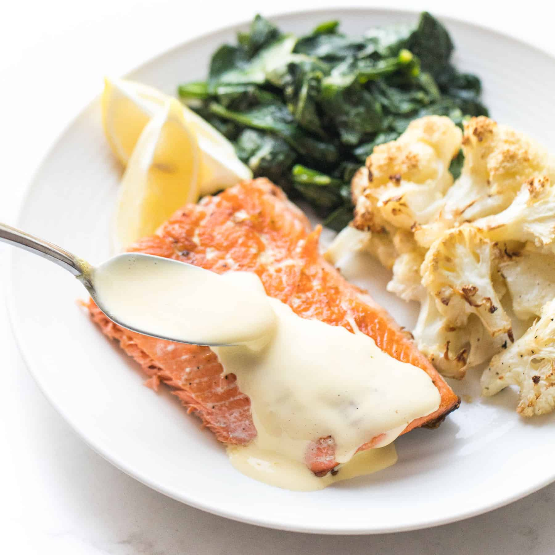 salmon with hollandaise sauce with roasted cauliflower and cooked spinach on a white plate