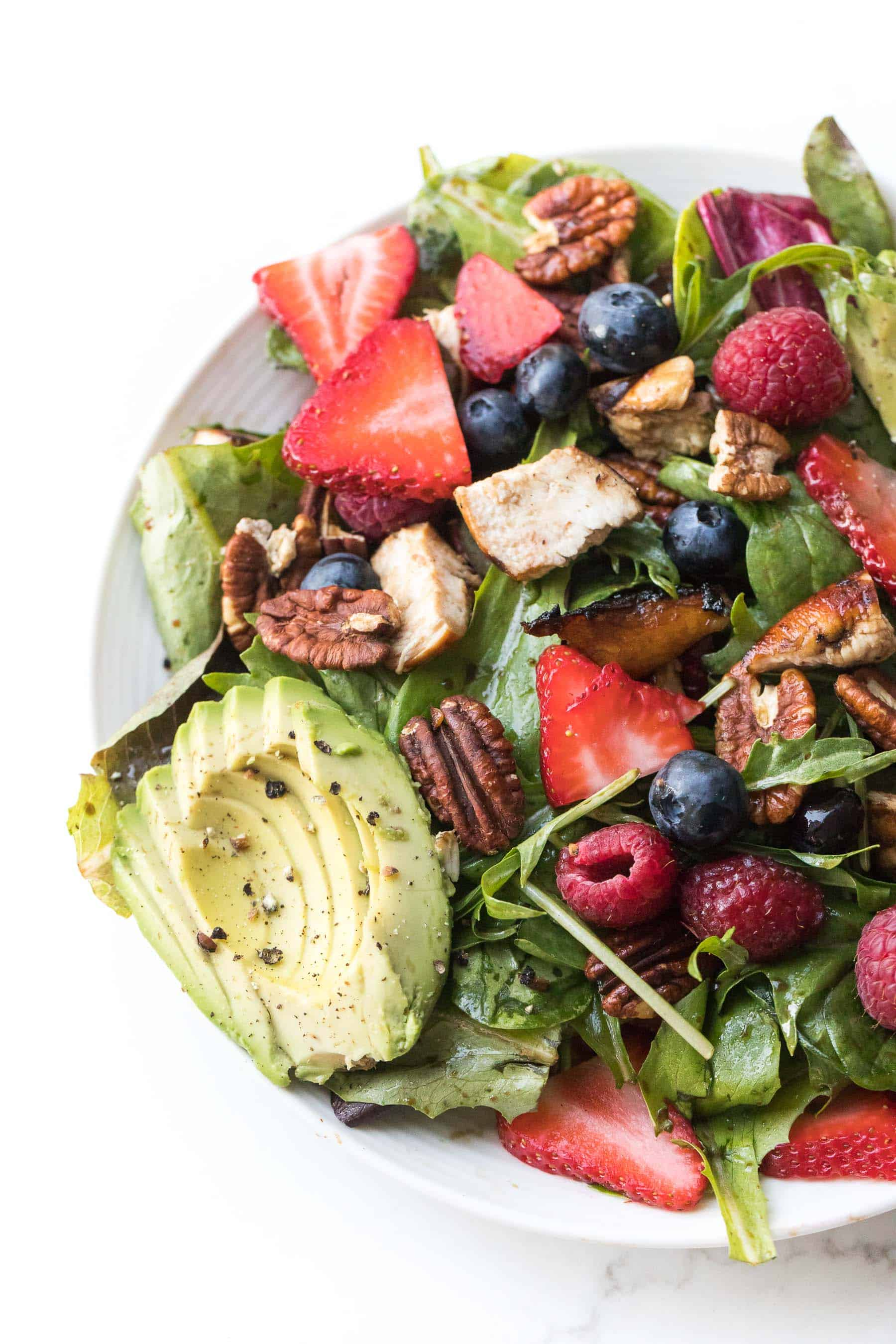 salad with strawberries, blueberries, raspberries, chicken, avocado + pecans on a white plate and background