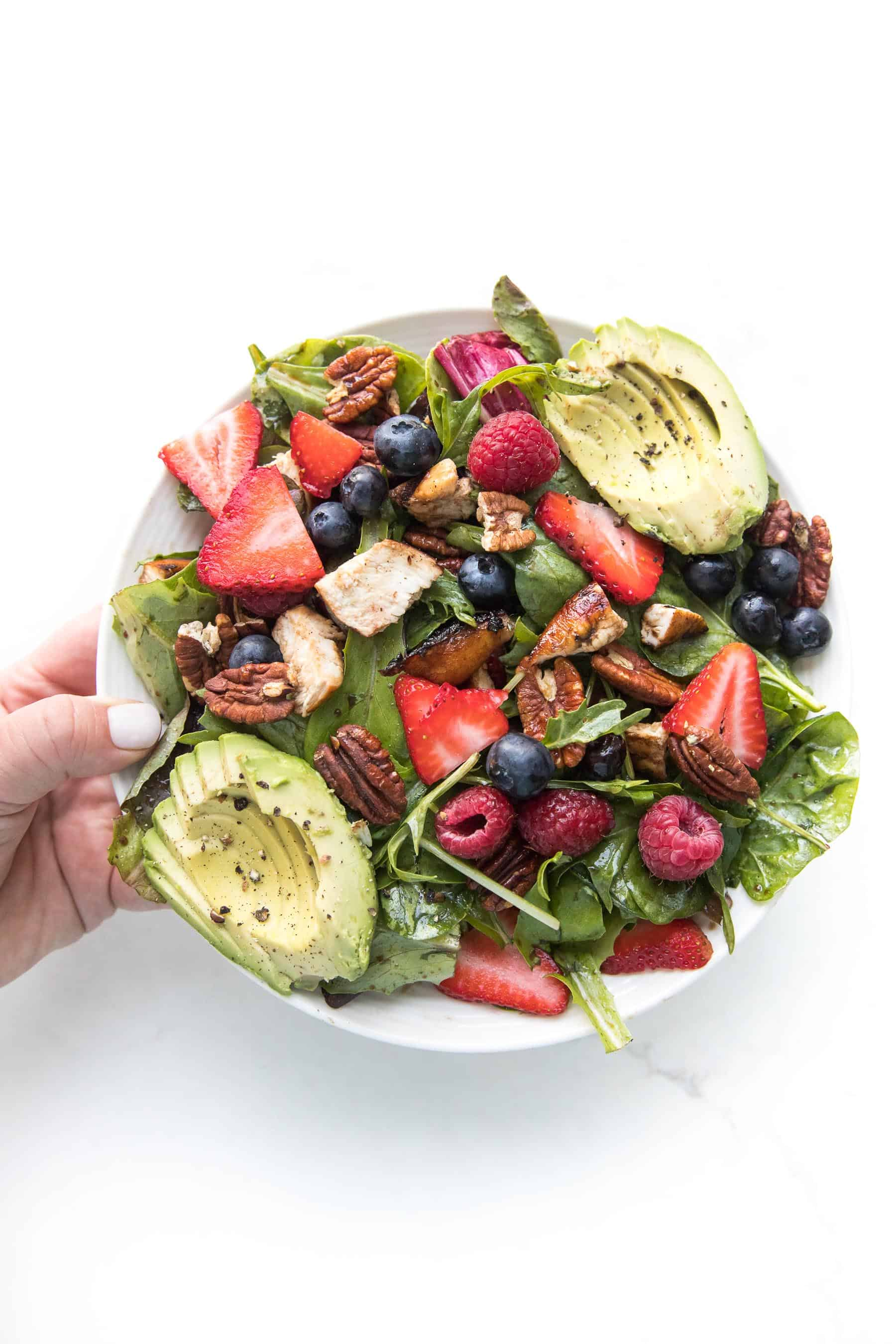 hand holding a salad with strawberries, blueberries, raspberries, chicken, avocado + pecans on a white plate and background
