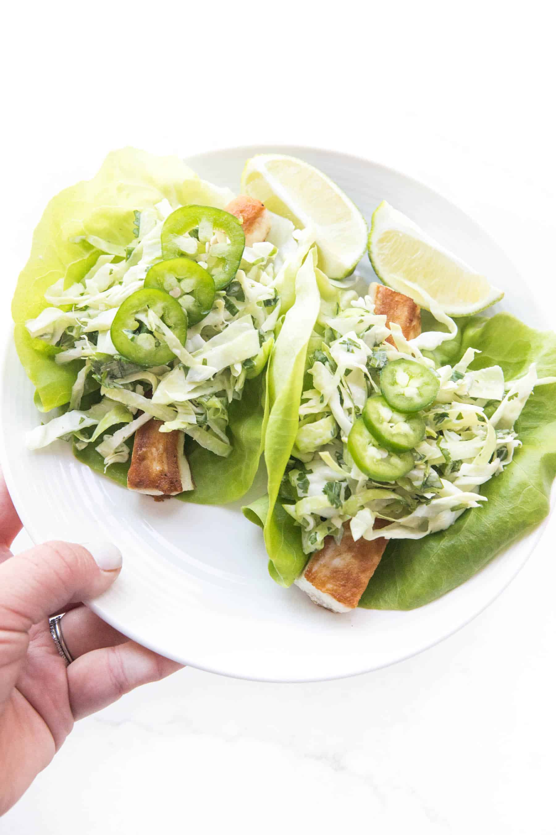 hand holding fish tacos on a lettuce taco shell topped with coleslaw on a white background