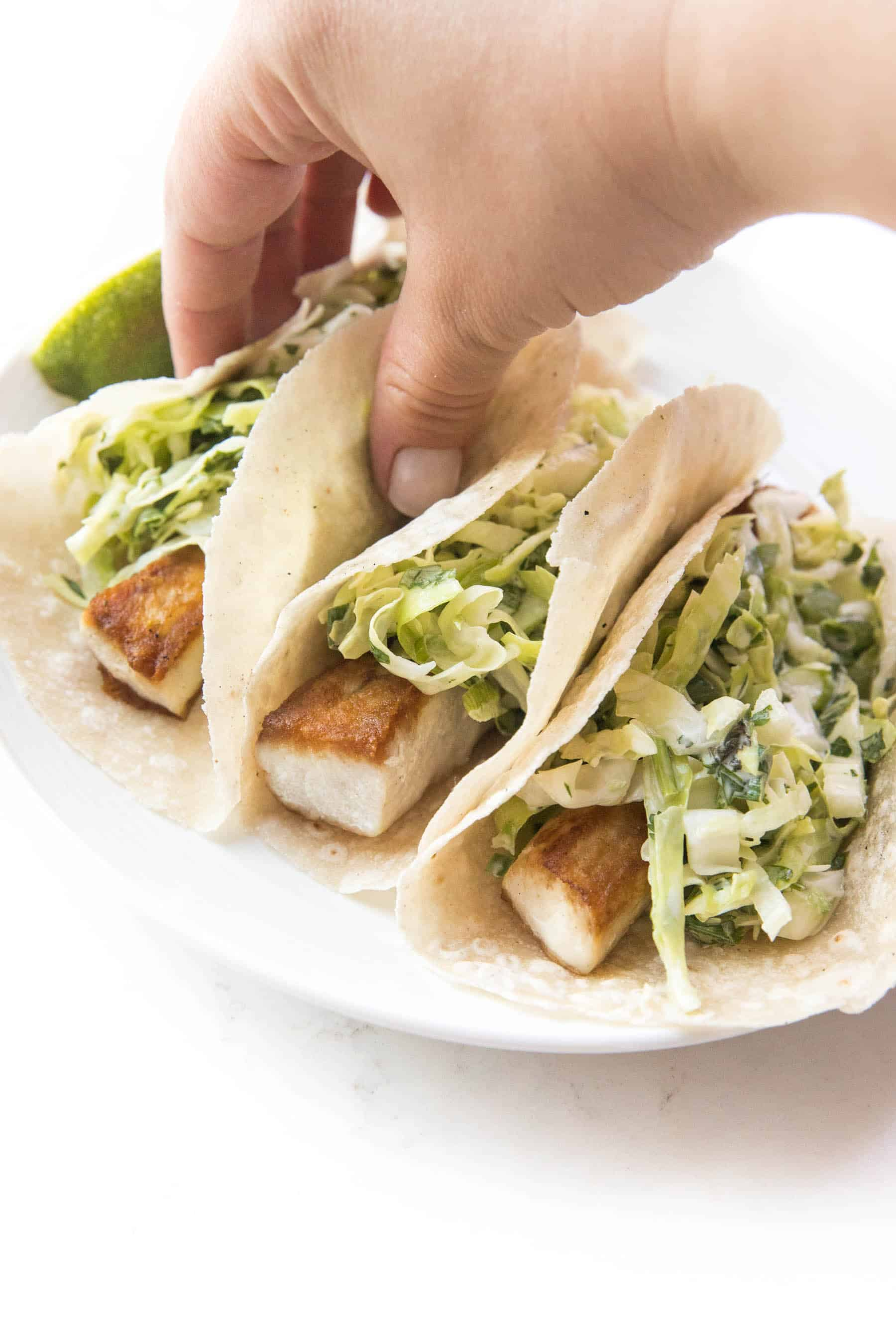 hand grabbing a fish tacos topped with coleslaw on a white background