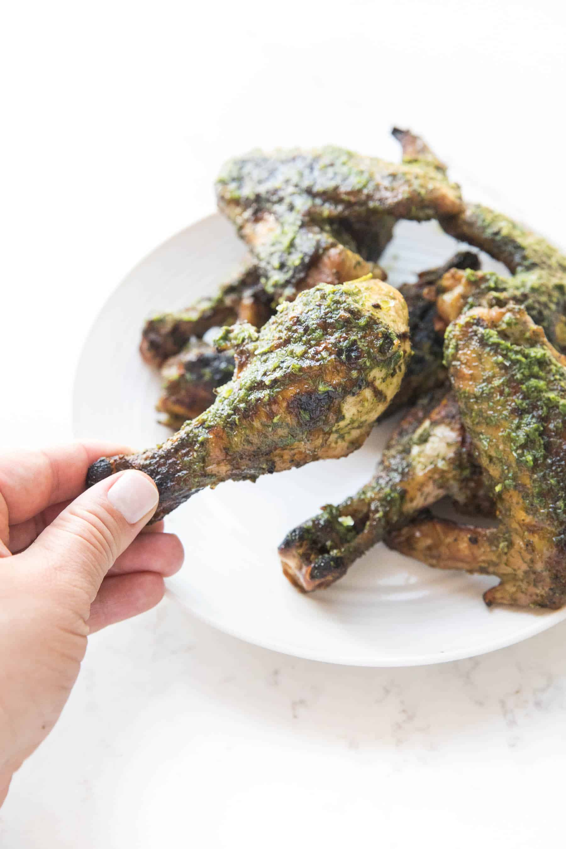 hand holding chicken drumstick with chimichurri sauce on white background