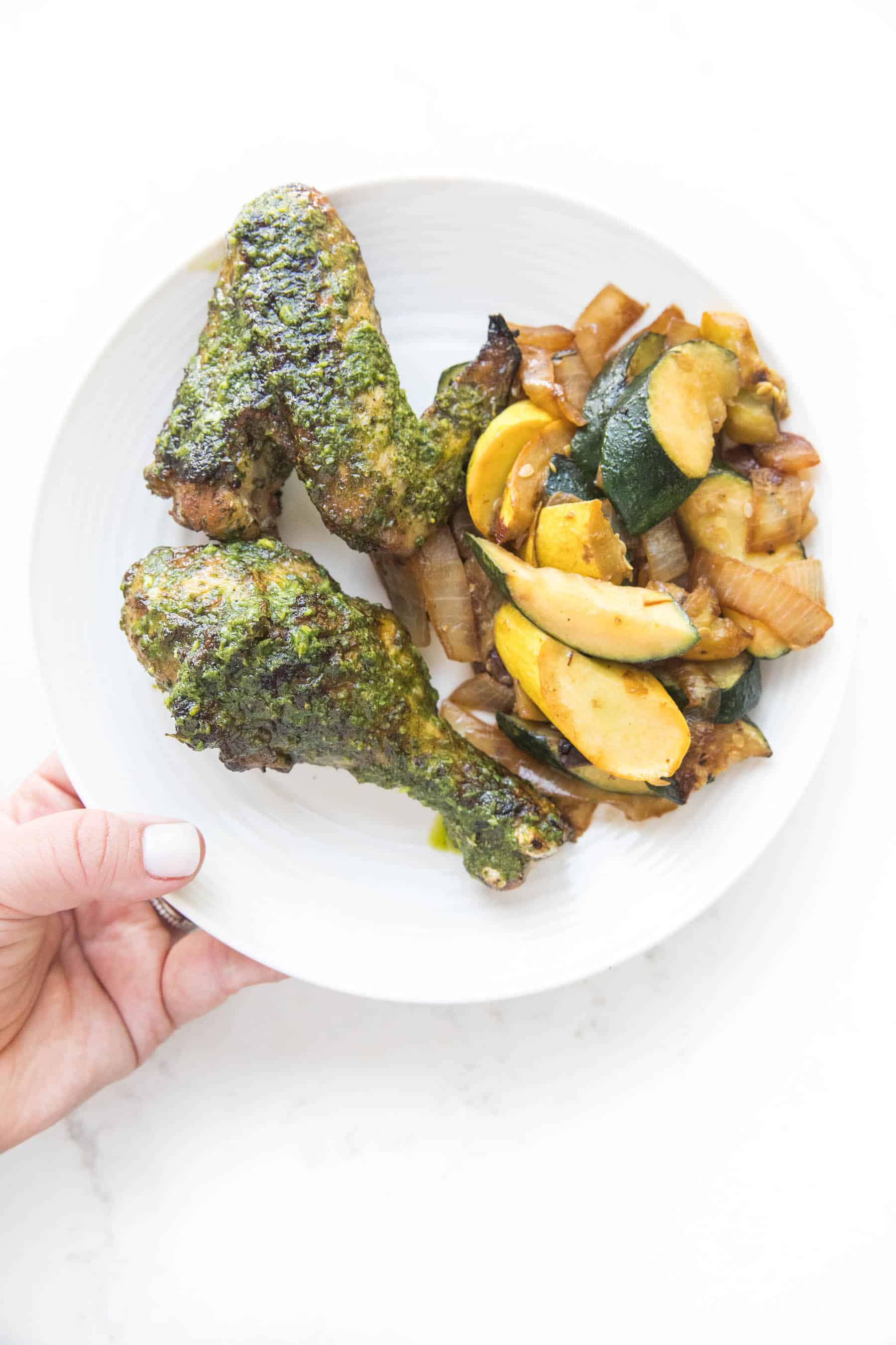 hand holding a white plate of grilled chicken with chimichurri chicken and squash on a white background