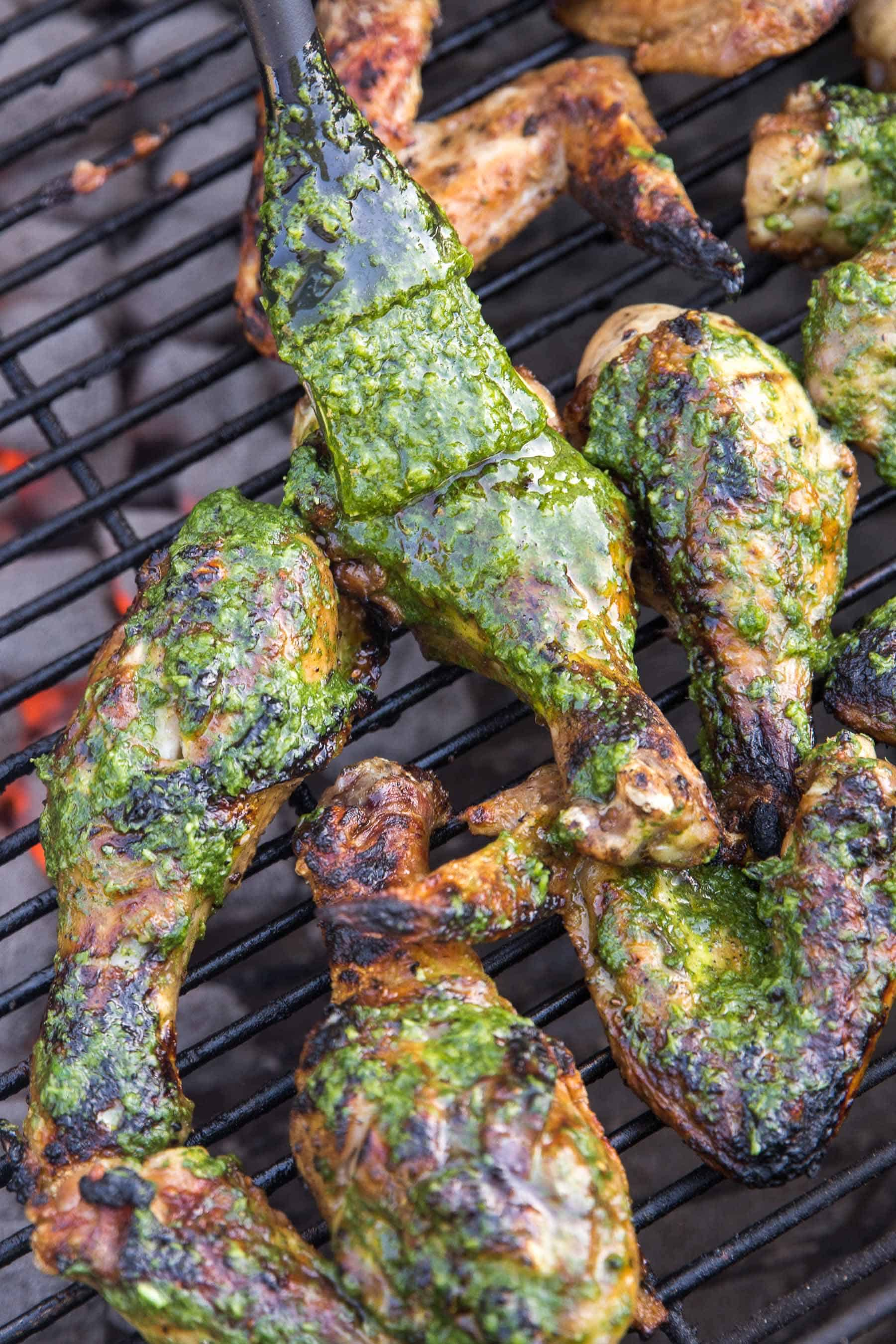 grilled chicken being brushed with green chimichurri sauce on a bbq