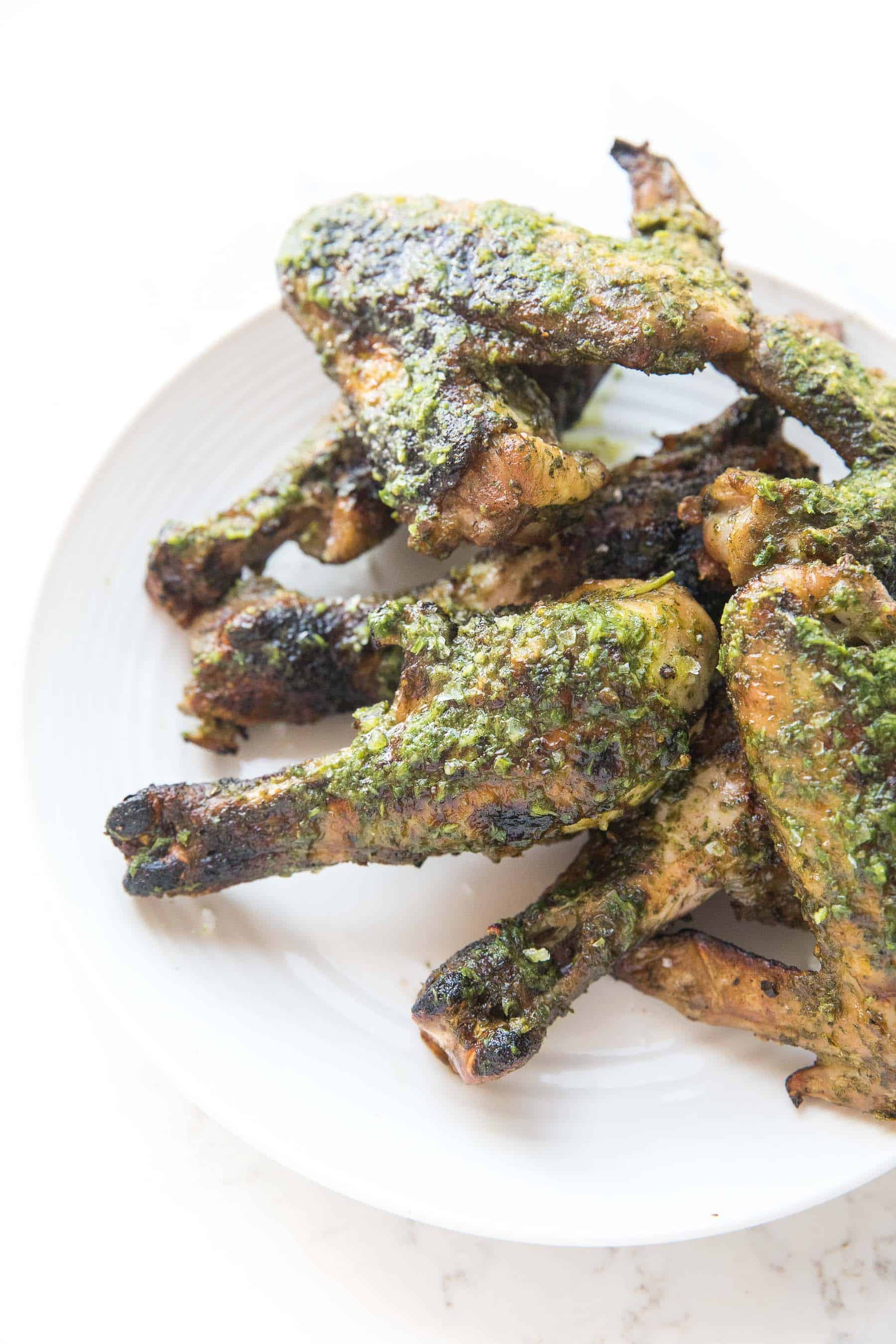 grilled chicken drumsticks and wings brushed with chimichurri sauce on a white background and white plate