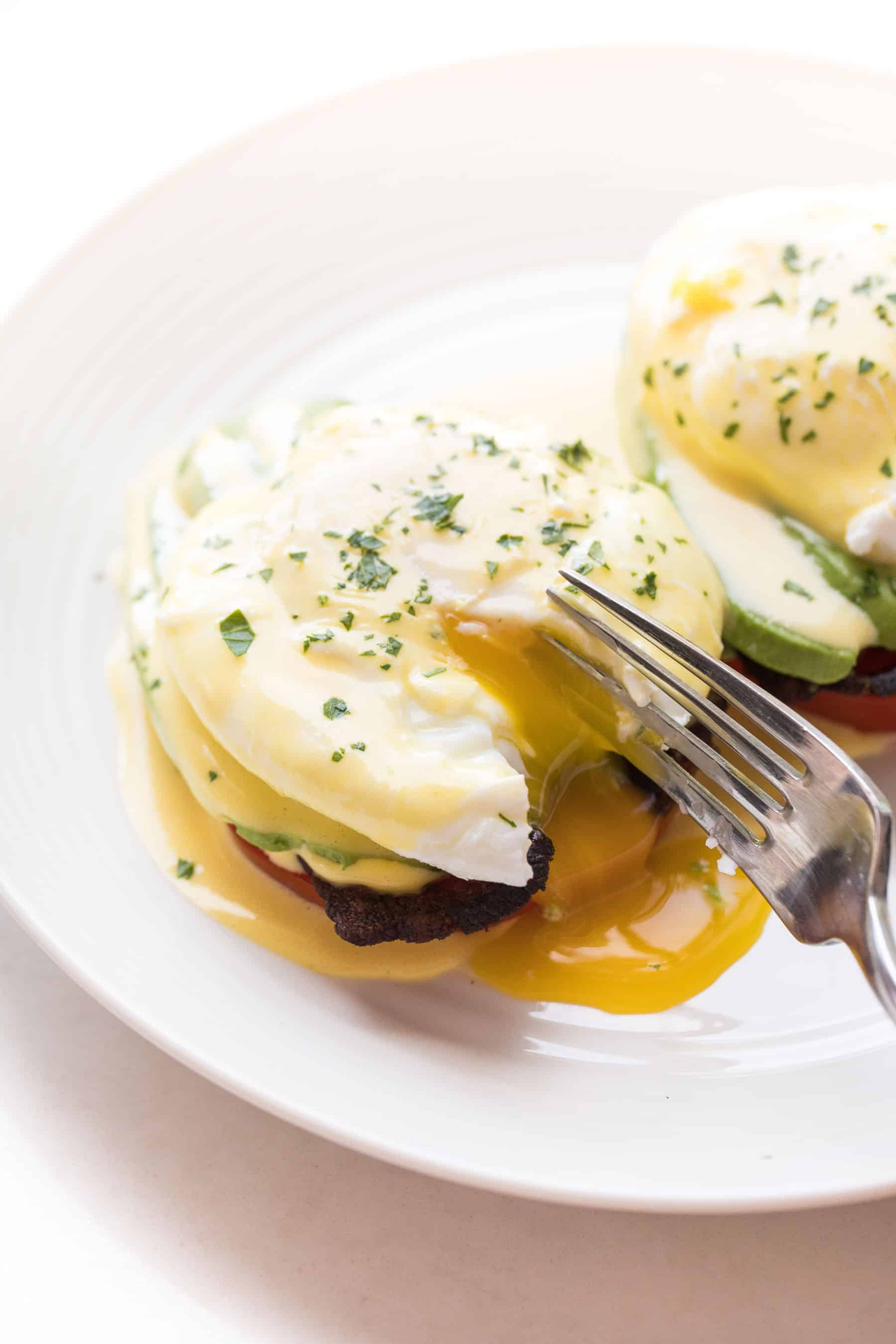 Fork cutting in to eggs benedict on a white plate