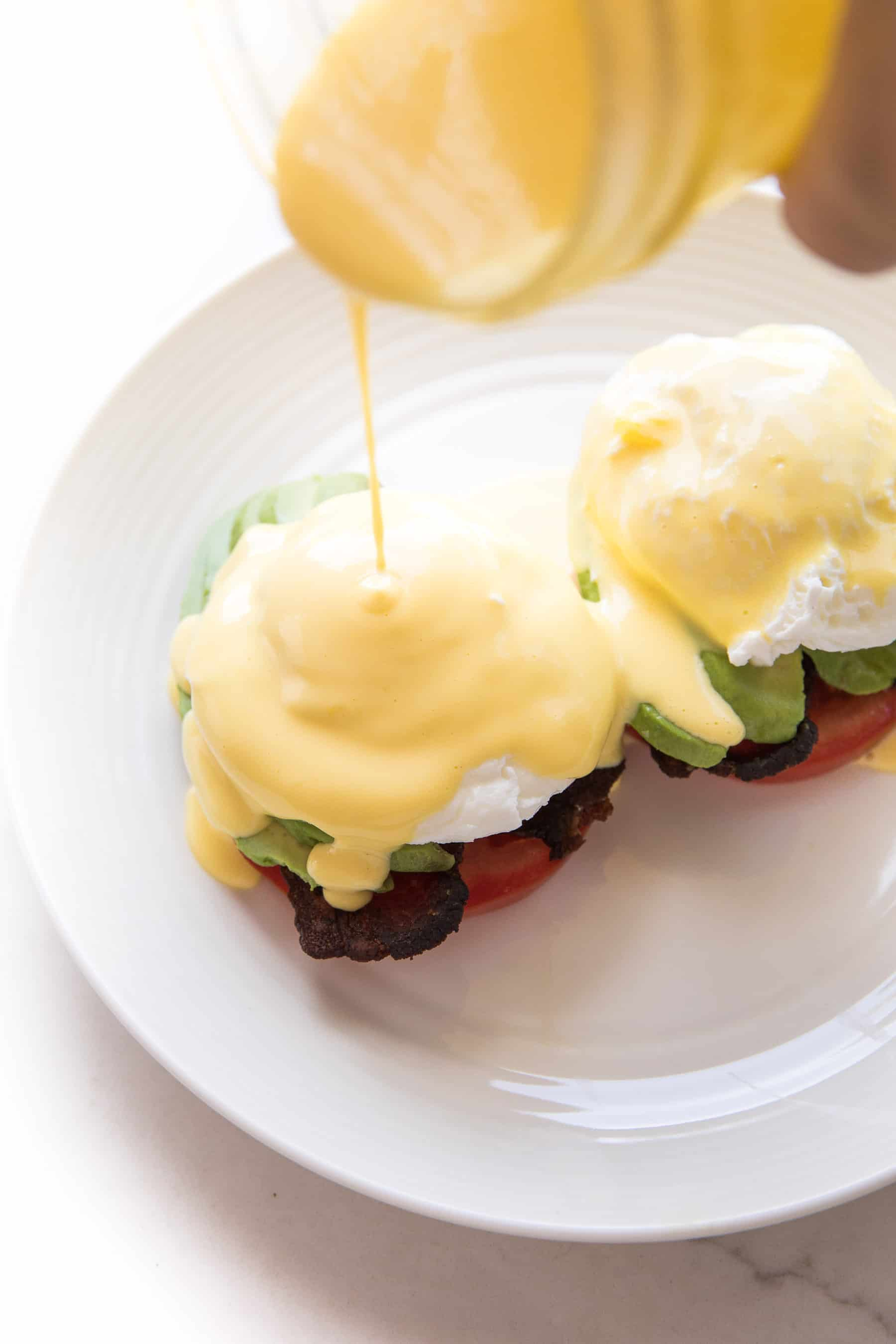 hollandaise sauce being poured over eggs benedict on a white plate
