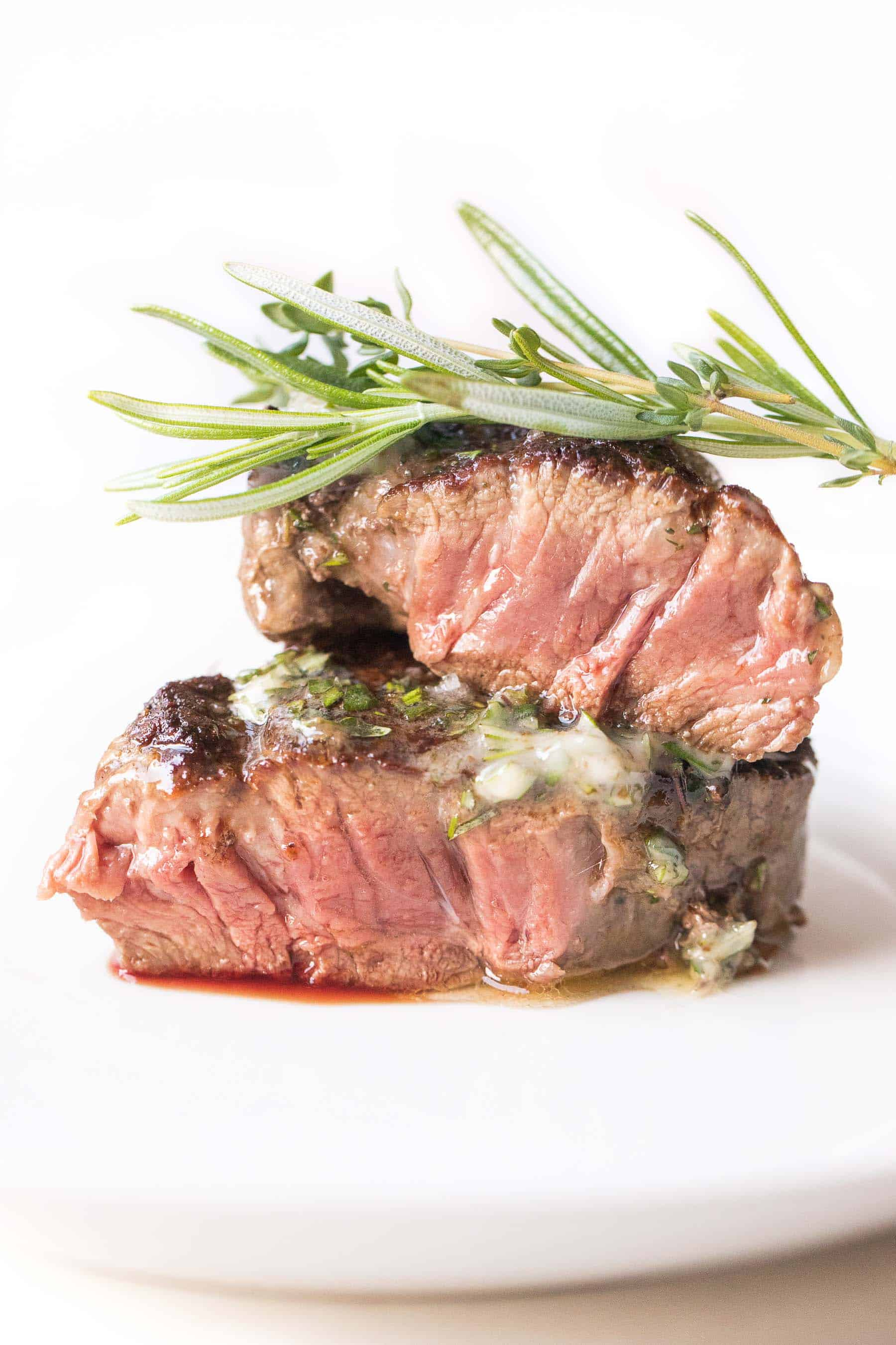 Filet mignon topped with herb butter on a white plate and white background