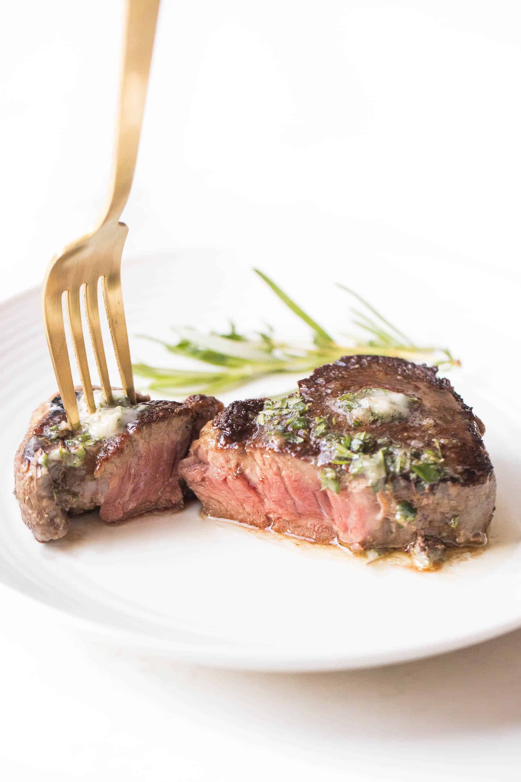 Filet mignon cut in half topped with herb butter on a white plate and white background