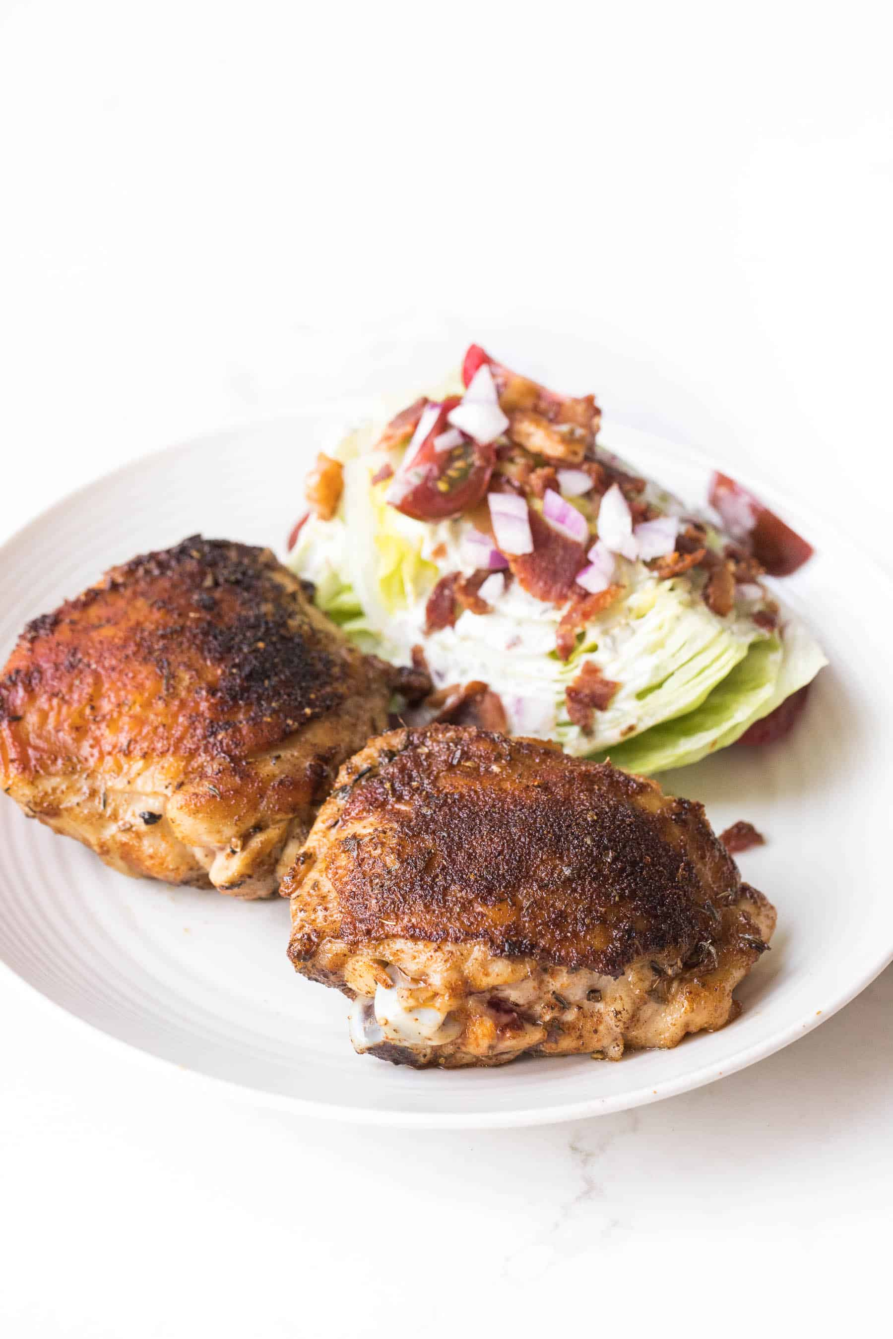cajun chicken thighs with a wedge salad on a white plate and white background