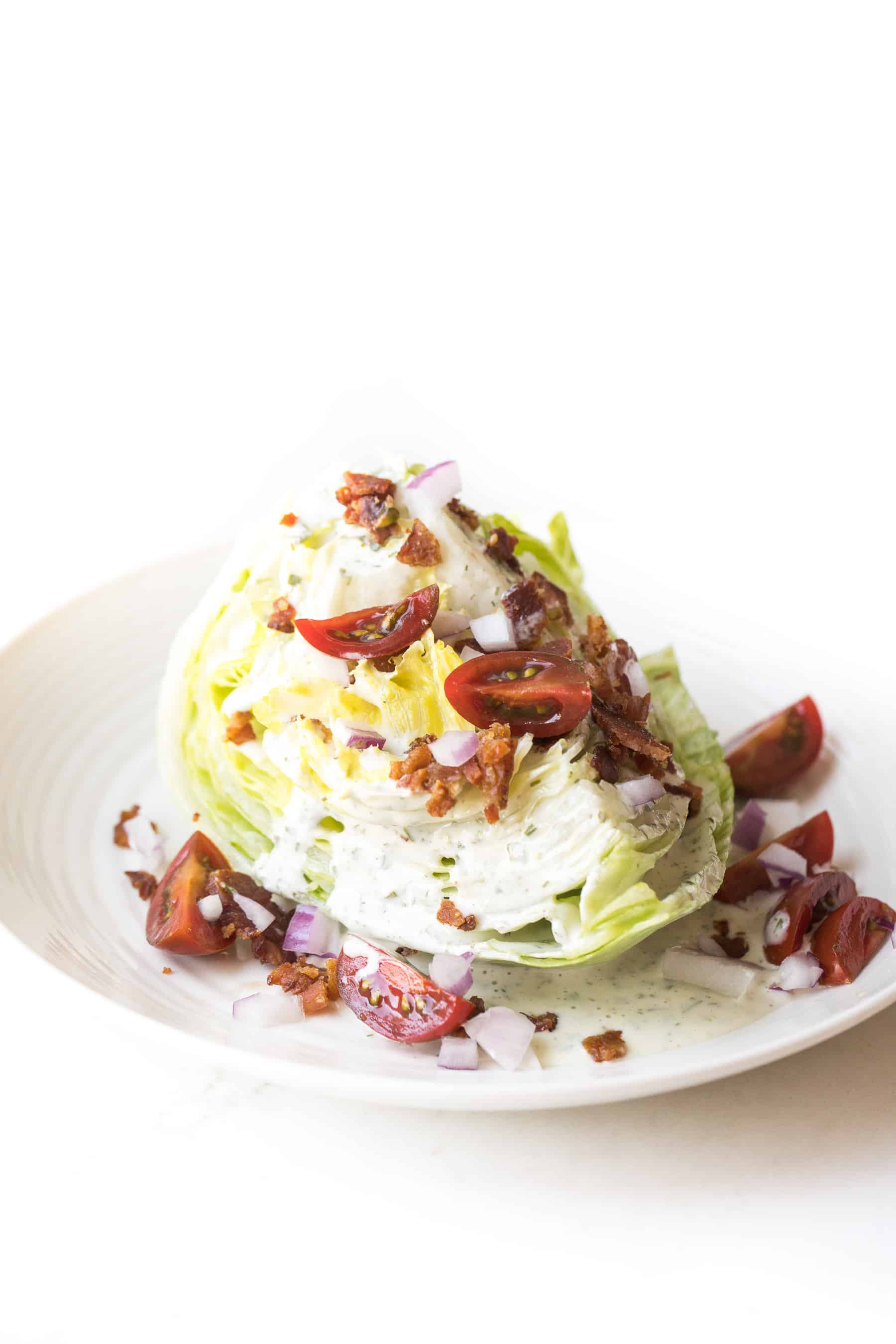 wedge salad topped with dressing, bacon, tomatoes and onion on a white plate and white background
