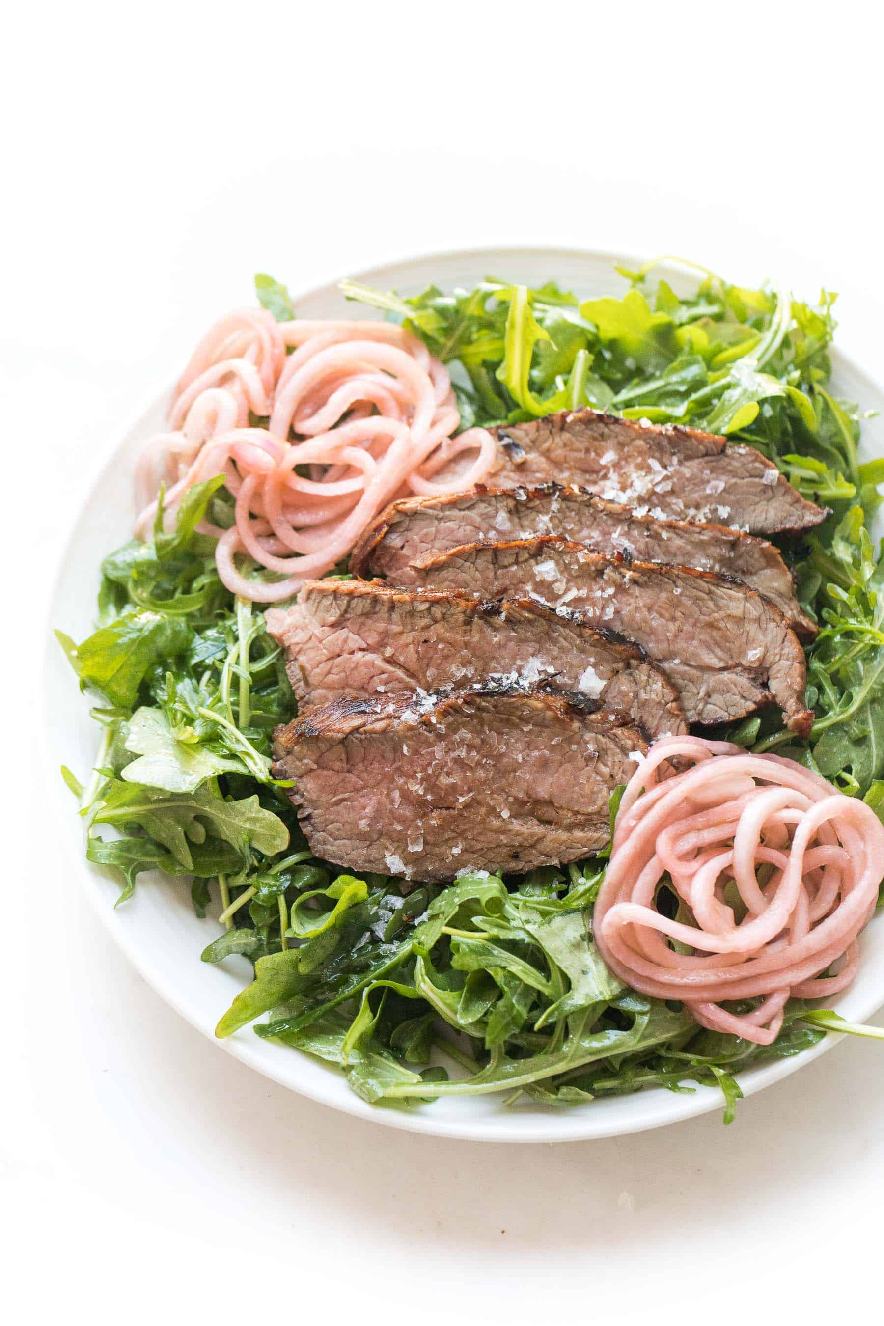 Tri tip arugula salad with pickled onions on a white plate and white background