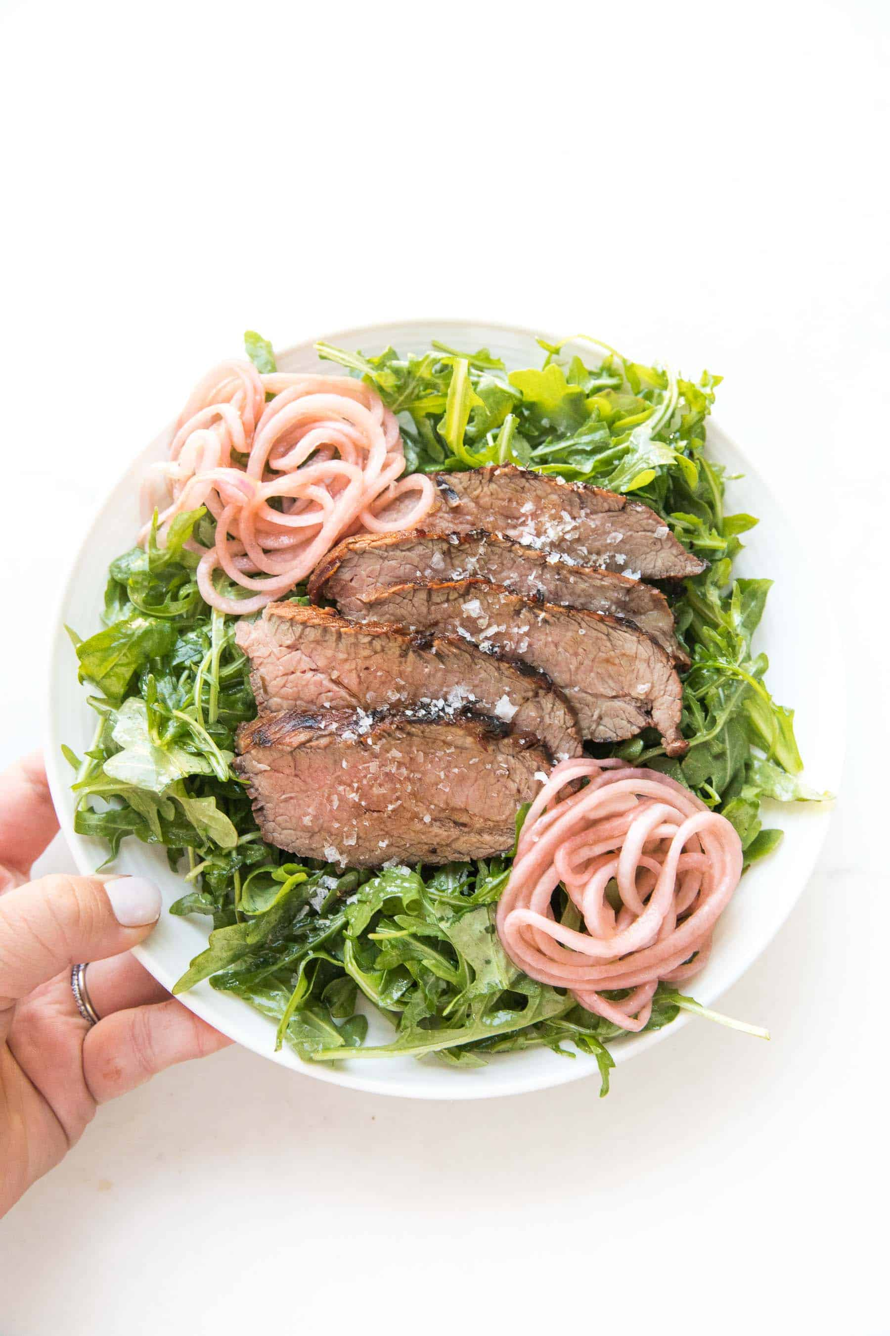 hand holding Tri tip arugula salad with pickled onions on a white plate and white background